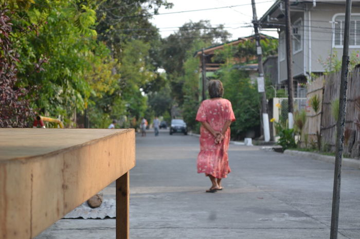Old lady walking away from camera in a Philippine village. Aging Filipino Old And New Philippines Senior Street Village Life Walking