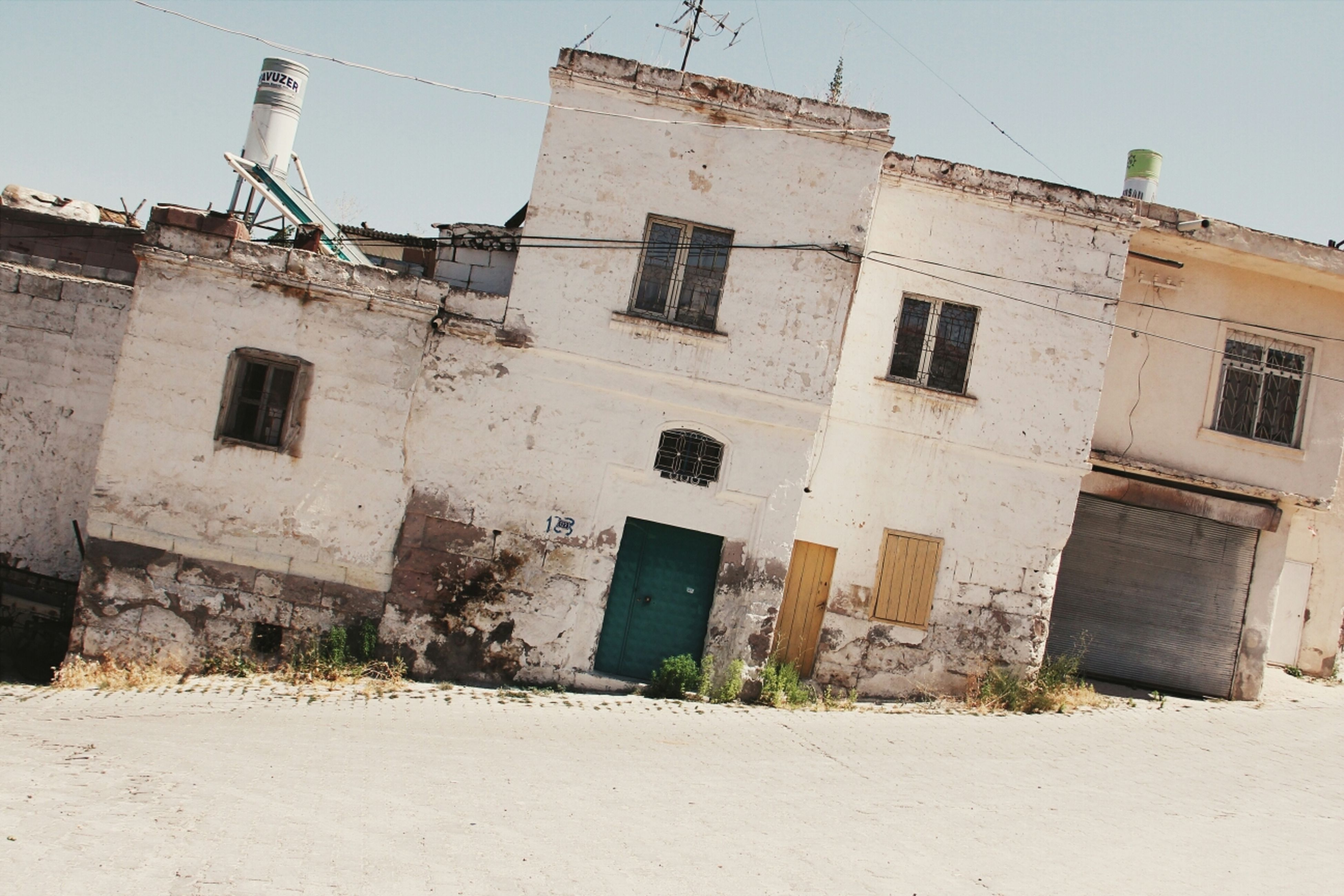 building exterior, architecture, built structure, low angle view, window, old, building, clear sky, residential building, residential structure, house, abandoned, damaged, obsolete, sky, weathered, day, run-down, outdoors, sunlight