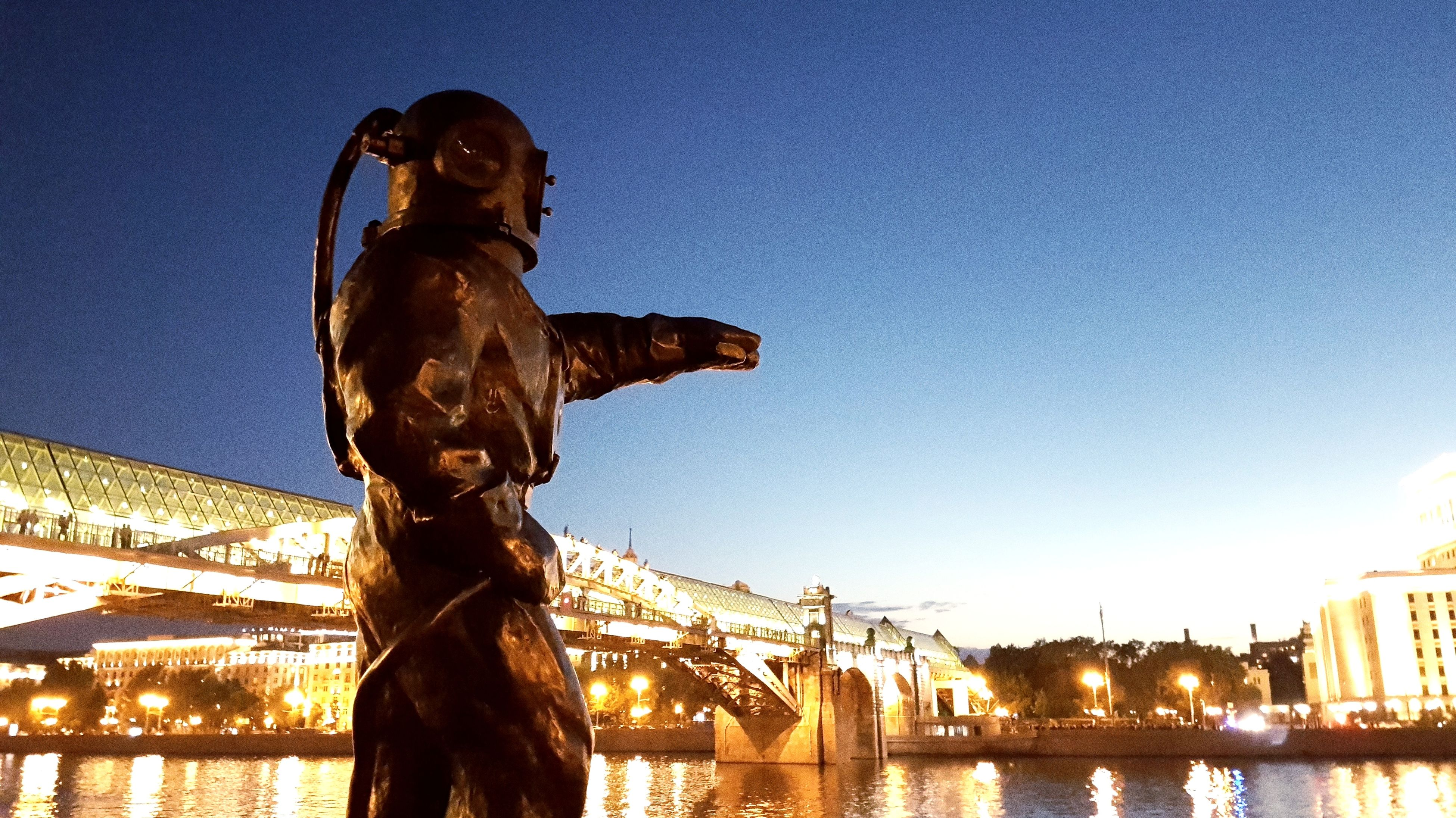 statue, sculpture, human representation, art and craft, built structure, architecture, bridge - man made structure, building exterior, travel destinations, outdoors, city, low angle view, clear sky, sky, water, no people, illuminated, day