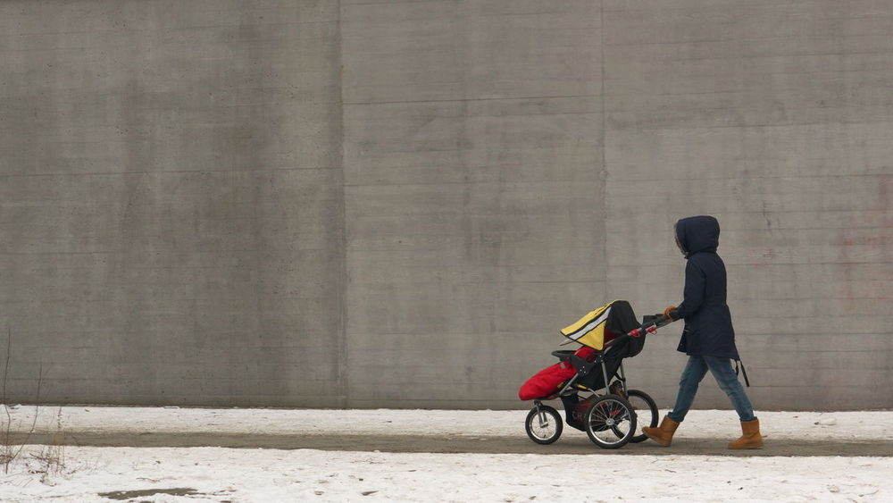 Woman with baby carriage in front of concrete wall in winter Adult Baby Carriage Clean Concrete Wall Day Men One Person Only Men Outdoors People Real People Side View Snow Winter Strassenfilm