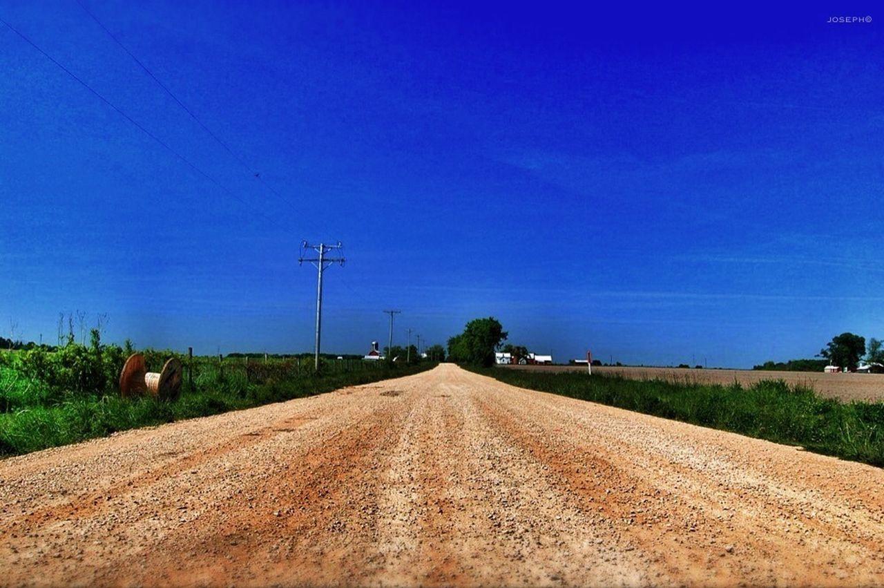field, blue, connection, landscape, nature, no people, rural scene, agriculture, road, day, the way forward, tranquil scene, outdoors, transportation, electricity pylon, technology, scenics, tranquility, beauty in nature, clear sky, sky, tree