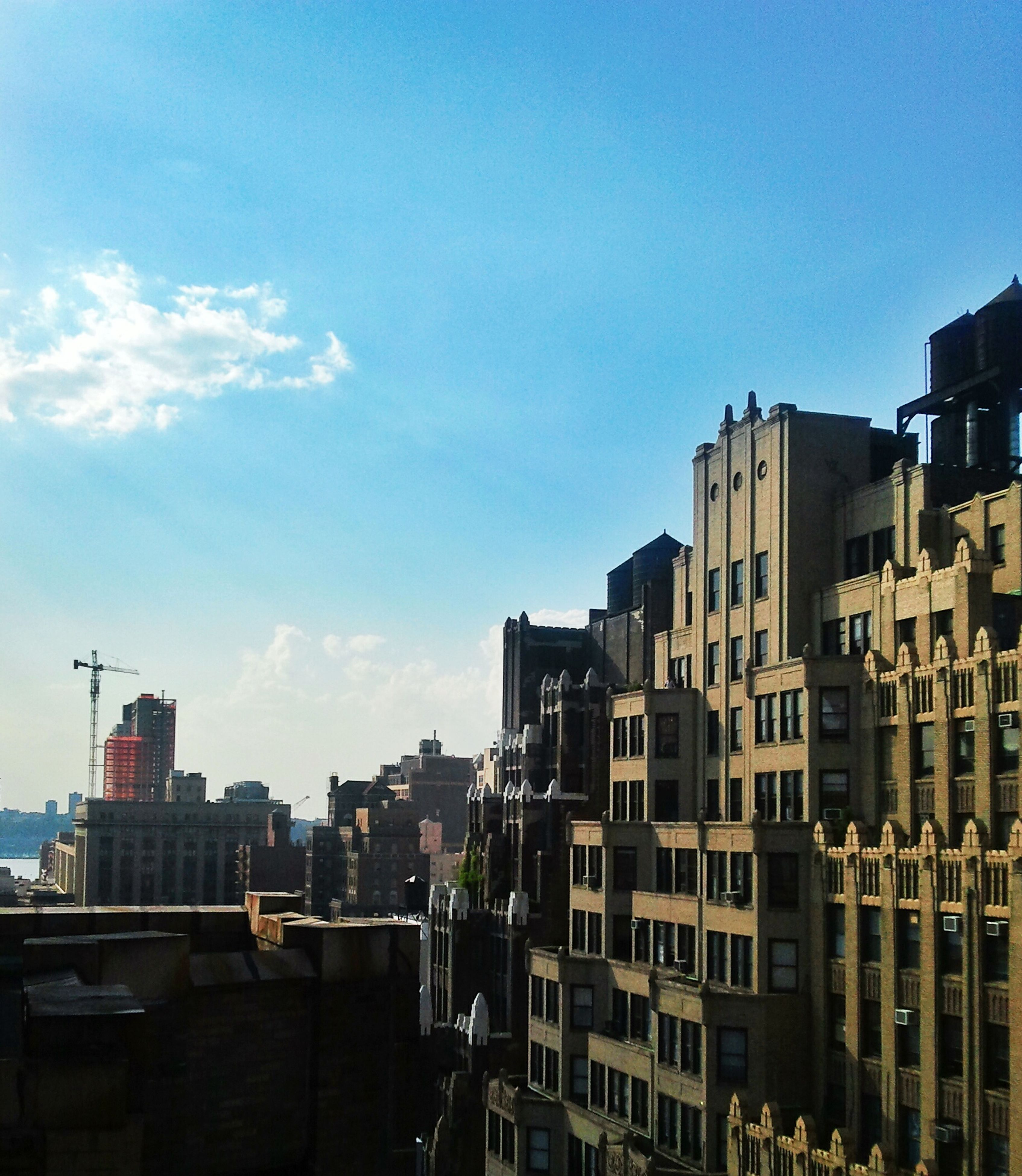 building exterior, architecture, built structure, city, residential building, sky, residential structure, blue, building, residential district, clear sky, house, day, sunlight, outdoors, cityscape, copy space, no people, town, city life