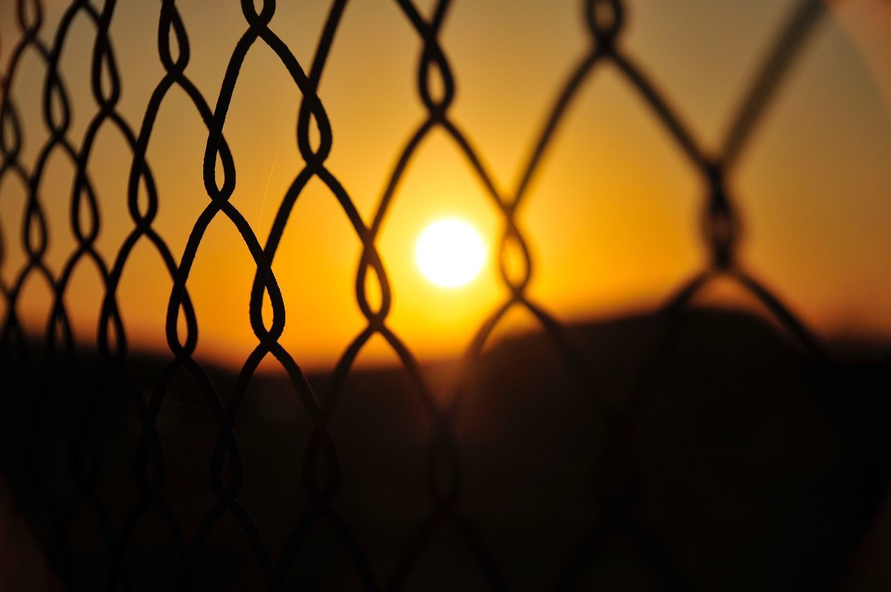 EyeEmNewHere Fence Chainlink Fence Security Sunset Protection Safety Silhouette Chainlink Metal Pattern Sunlight No People Focus On Foreground Dusk Close-up Orange Color Sky Outdoors Wire Mesh City