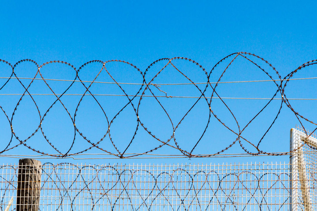Barbed Wire Fence Barbed Wire Blue Blue Sky Chainlink Fence Clear Sky Close-up Danger Day Exclusion Fence Horizontal Looking Up Metal No People Outdoors Prison Protection Razor Wire Robben Island Safety Security Security System Sky Spiral Water