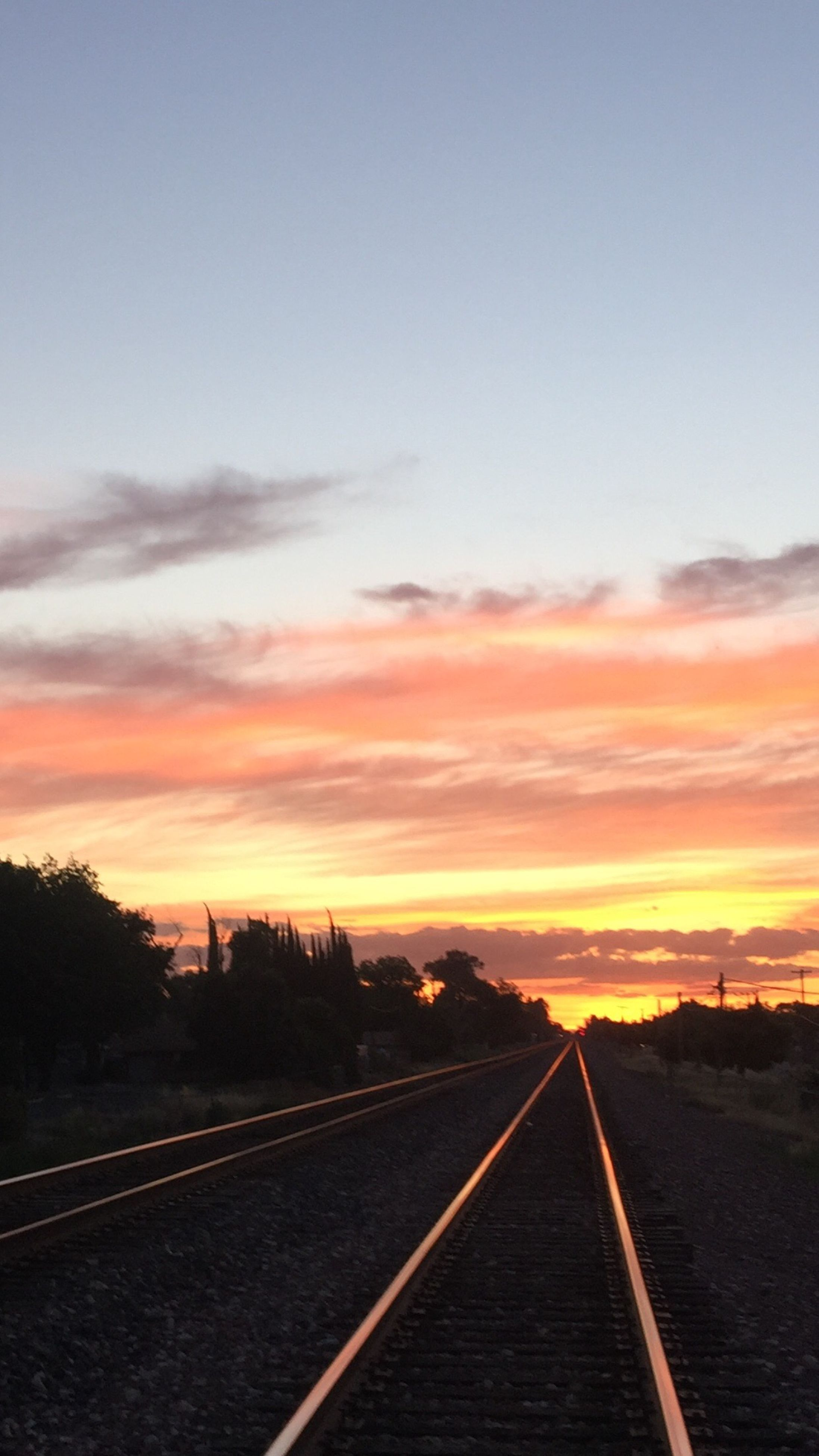 the way forward, railroad track, transportation, sunset, diminishing perspective, sky, vanishing point, rail transportation, orange color, cloud - sky, road, straight, landscape, tranquil scene, tranquility, long, nature, dusk, outdoors, no people