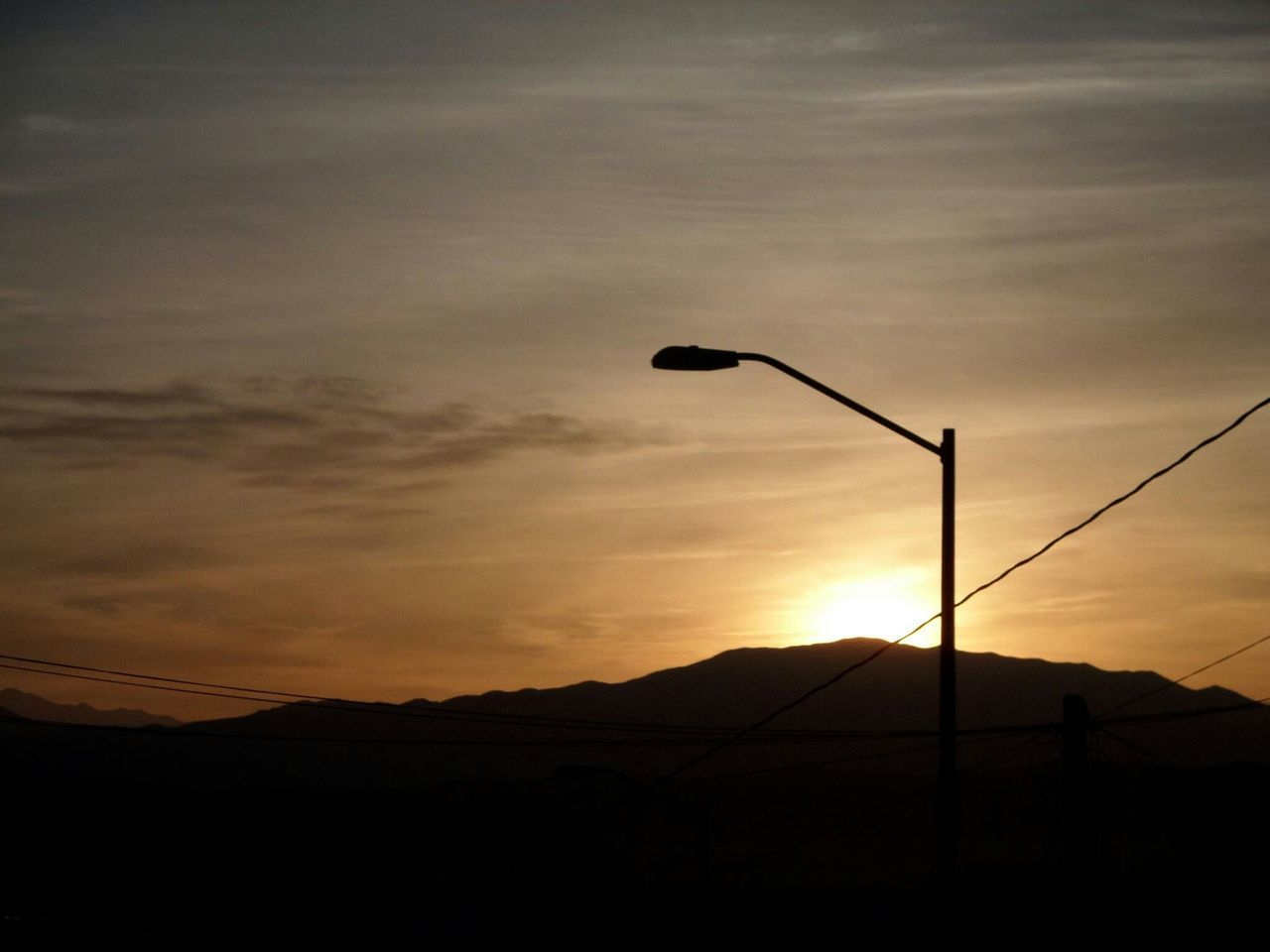 Low Angle View Of Street Light And Mountains Against Sky During Sunset