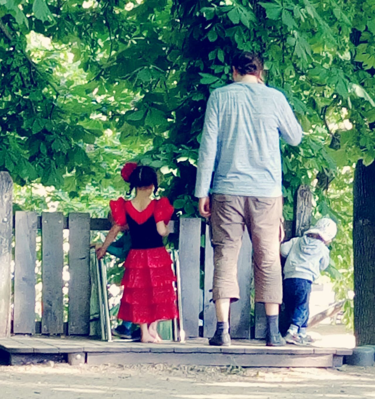 Rear View Togetherness Adult Walking Full Length Mid Adult People Casual Clothing Day Family With One Child Love Outdoors Men Child Father Bonding Leisure Activity Human Body Part Tree Playground Warm Weather Urban Lifestyle Low Section Red Dress Flamenco Dress