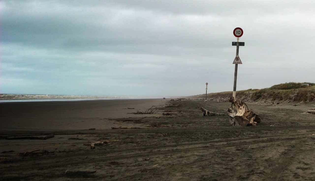 Beach Beauty In Nature Cloud - Sky Day Driftwood Nature No People Outdoors Sand Sea Sky Speed Limit Sign Water
