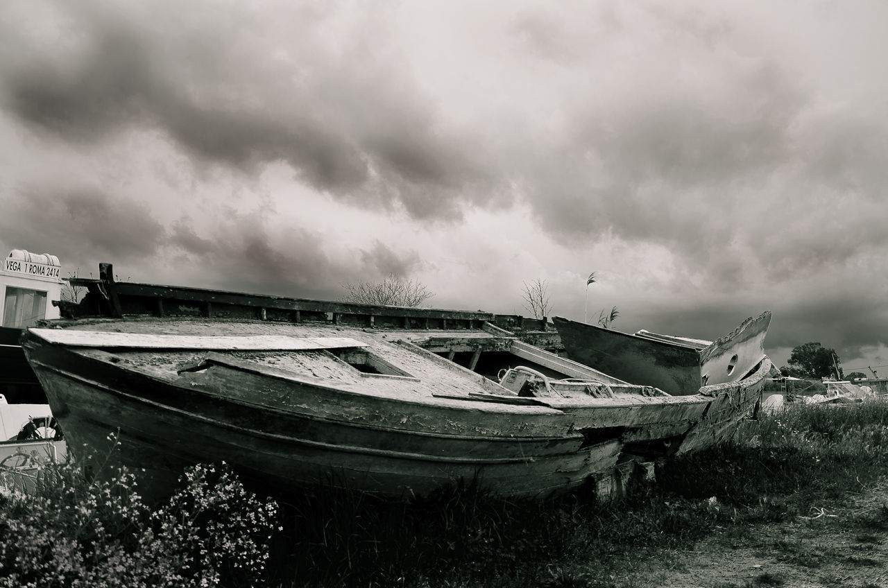Abandoned Boat On Field Against Cloudy Sky