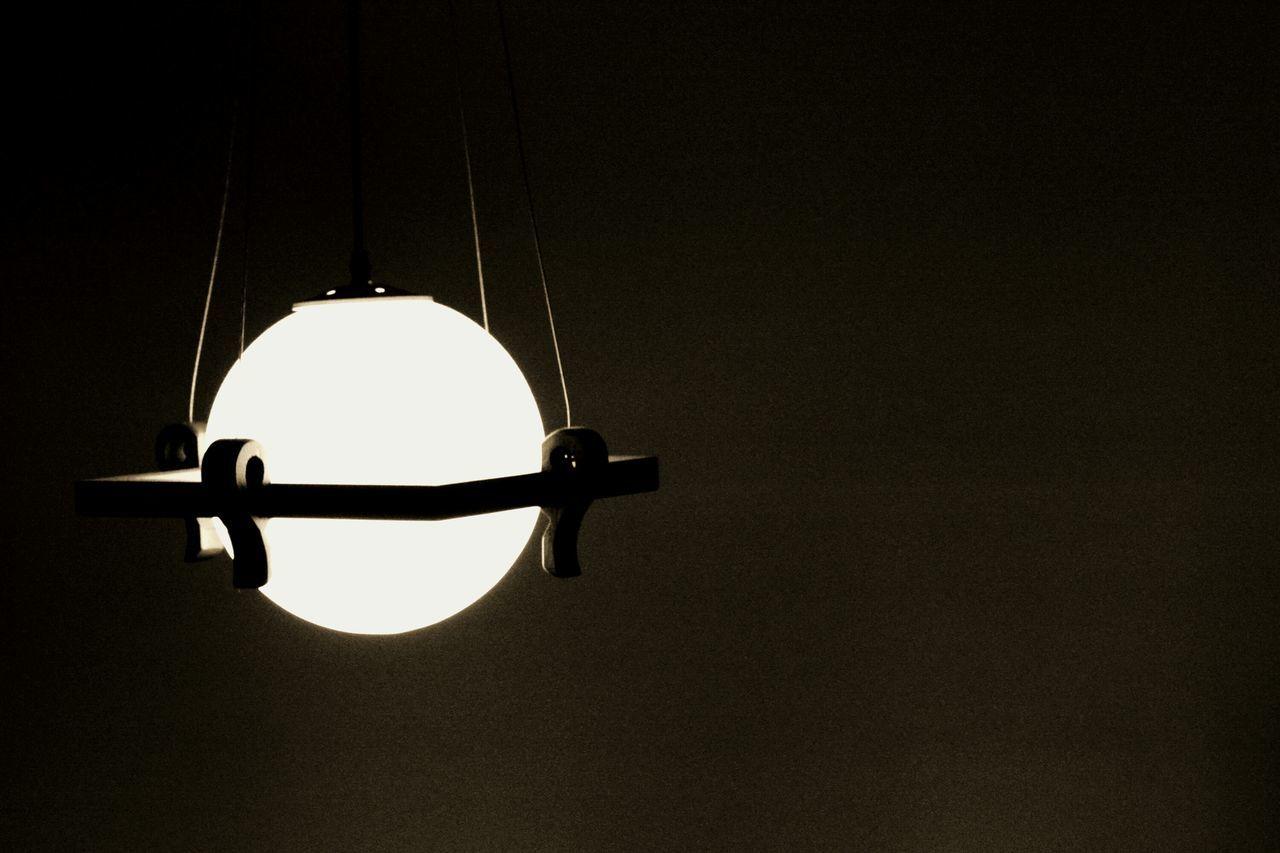 Illuminated Electric Lamp Hanging In Dark Room