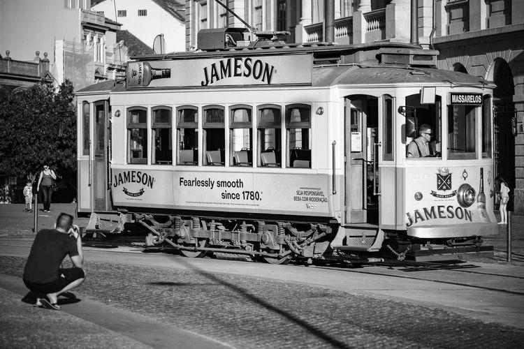 The tourist Adult City Day Horizontal Jameson Man Mode Of Transport Monochrome Photography Outdoors People Public Transportation Text Train - Vehicle Tram Tramway Transportation Travel