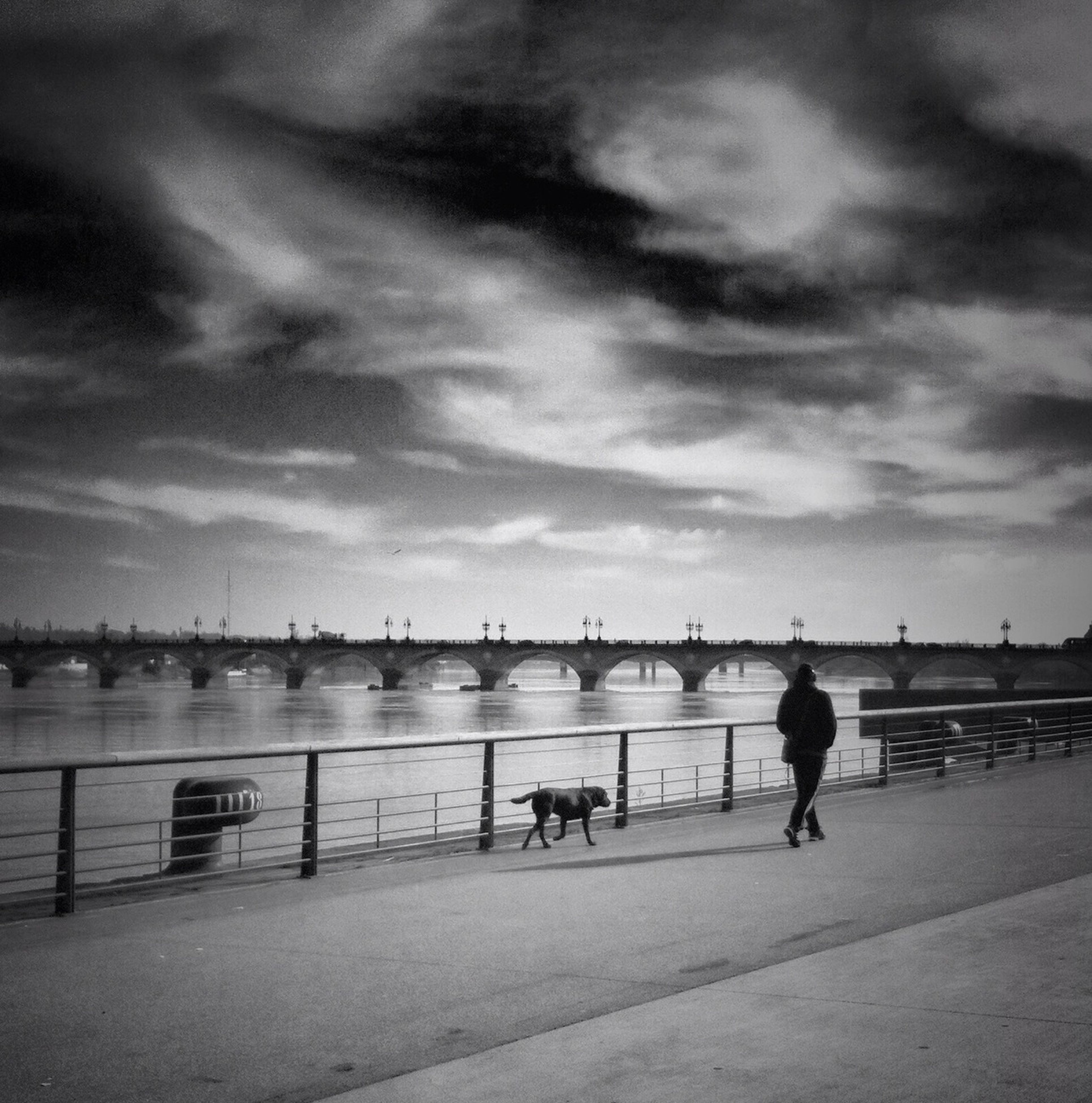 water, sky, cloud - sky, sea, railing, men, walking, rear view, lifestyles, pier, full length, cloudy, cloud, lake, leisure activity, person, river, the way forward, nature