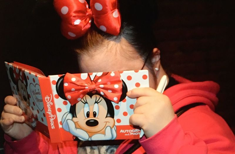 Lost in her autograph book Disney One Person Real People Celebration Lifestyles Red Wearing Christmas Indoors  Human Hand Close-up Day People Disney