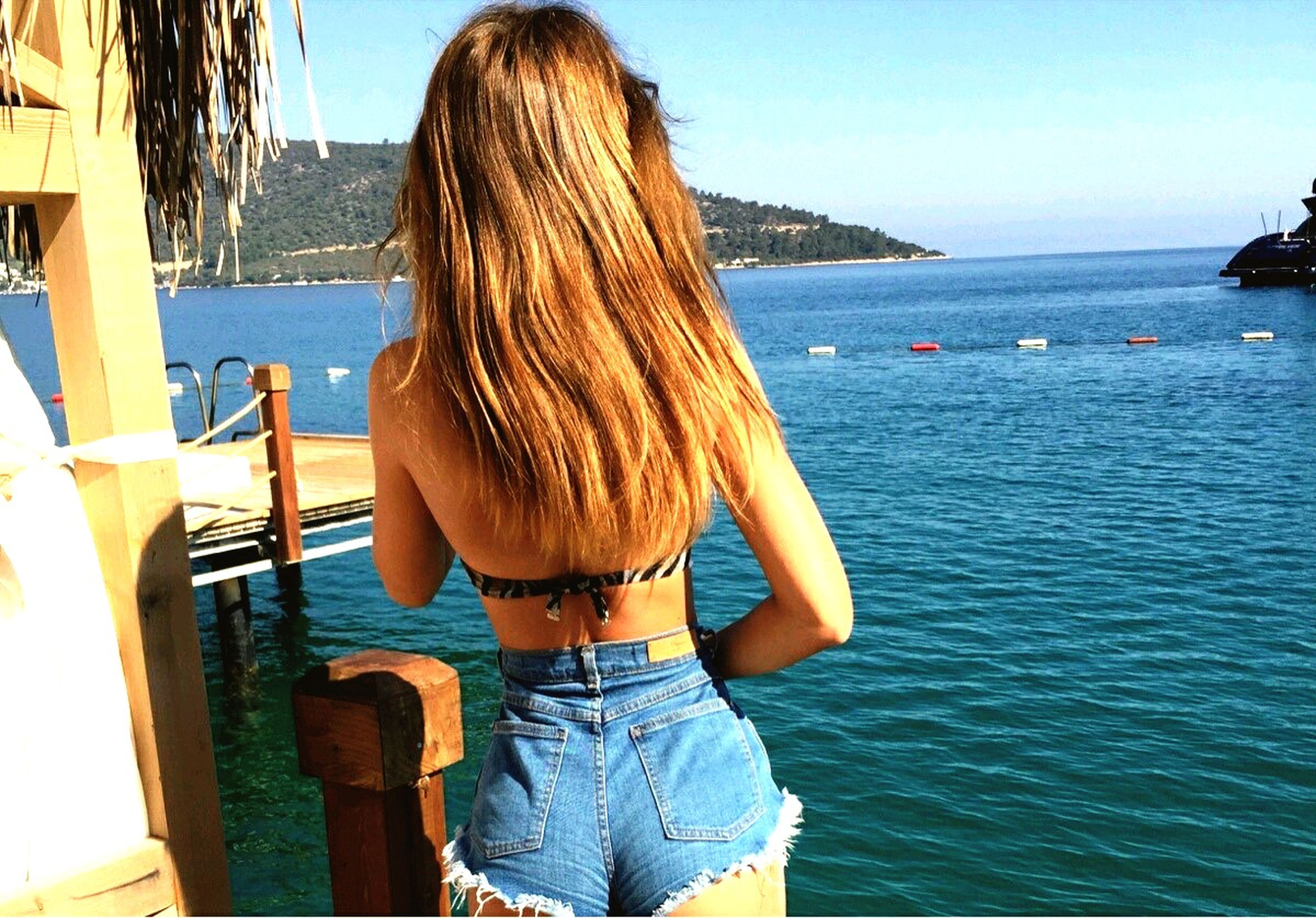sea, water, horizon over water, rear view, lifestyles, leisure activity, blue, long hair, clear sky, person, sky, standing, railing, beach, nature, tranquility, sunlight, scenics