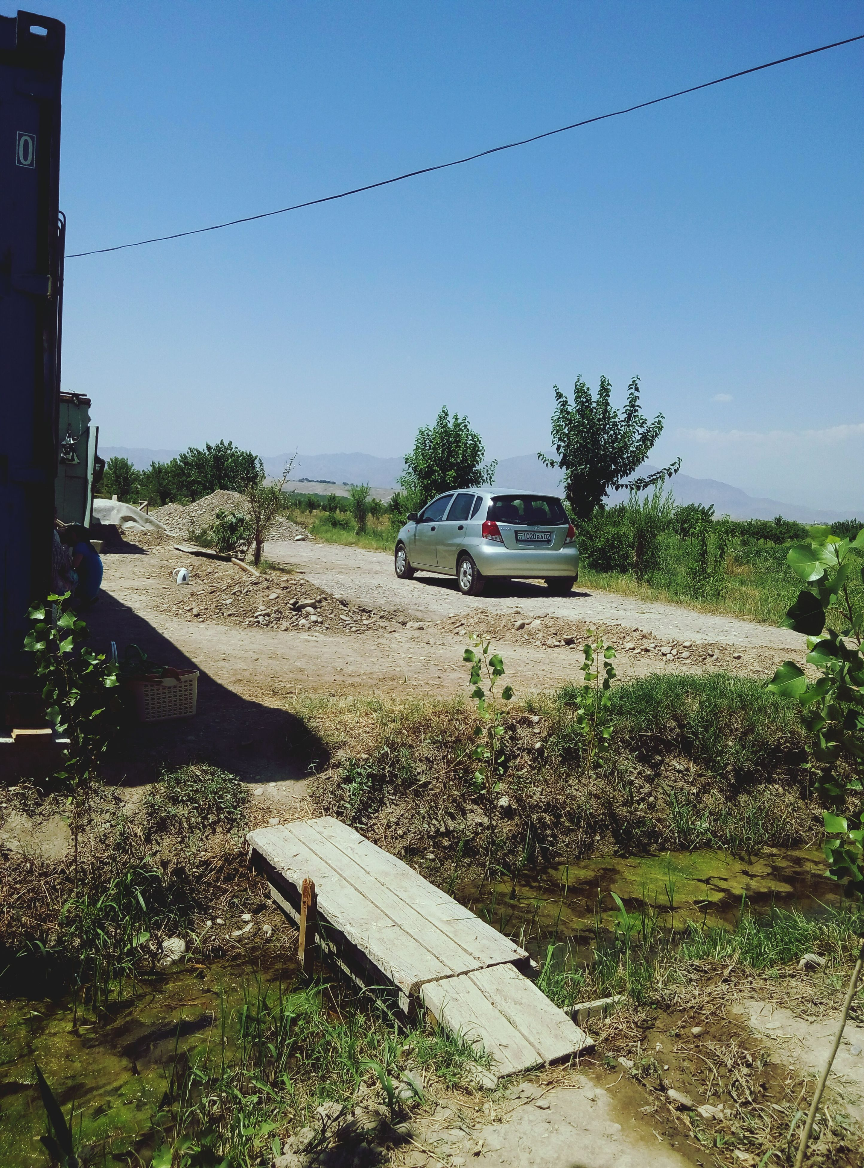 land vehicle, mode of transport, tree, road, sky, plant, sunlight, growth, grass, outdoors, day, nature, green color, no people, blue, stationary, parking, landscape, tranquility, rural scene, parked, the way forward