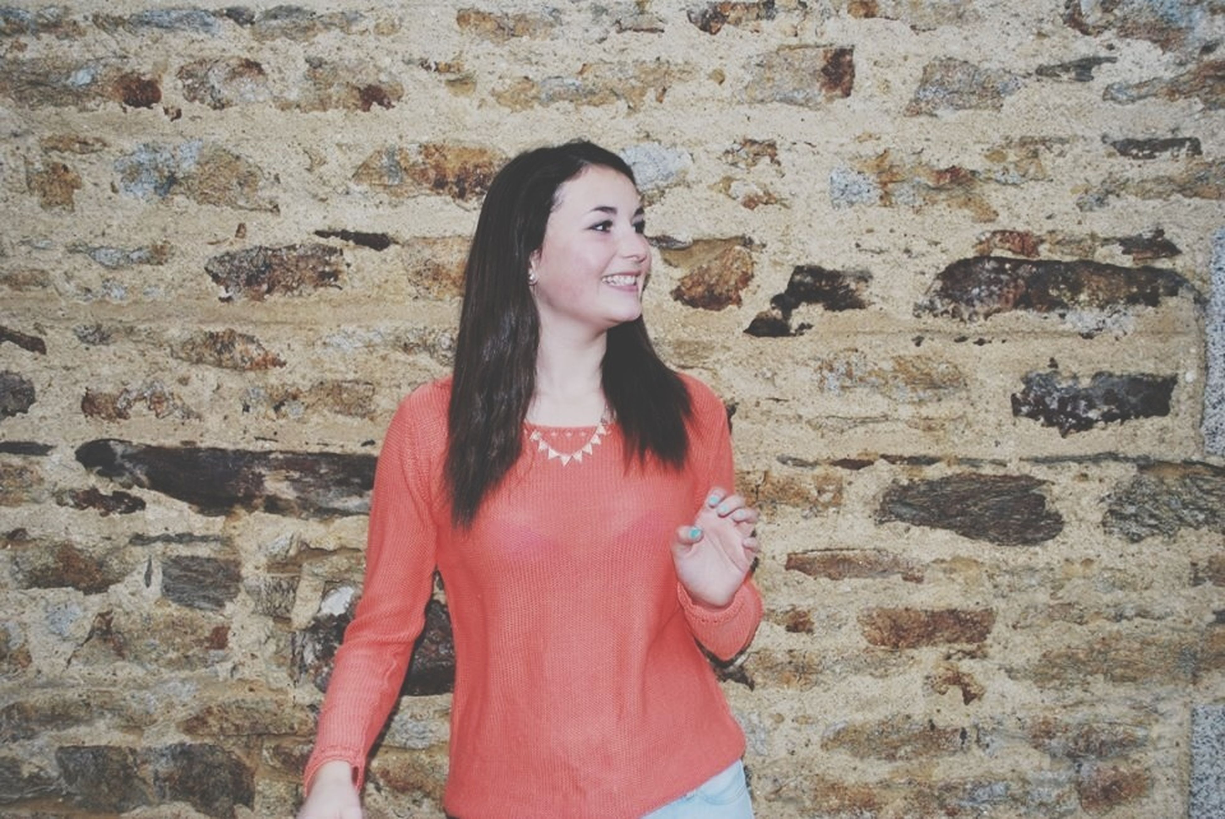 young adult, looking at camera, portrait, young women, person, lifestyles, front view, casual clothing, standing, leisure activity, smiling, wall - building feature, brick wall, long hair, three quarter length, waist up
