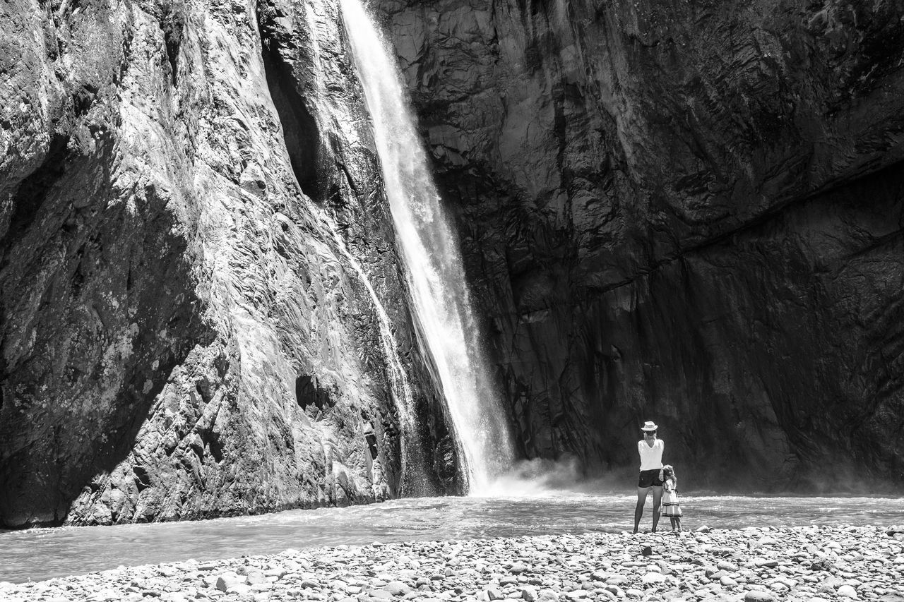 rock - object, one person, nature, real people, full length, waterfall, scenics, adventure, beauty in nature, standing, day, outdoors, water, people, adult