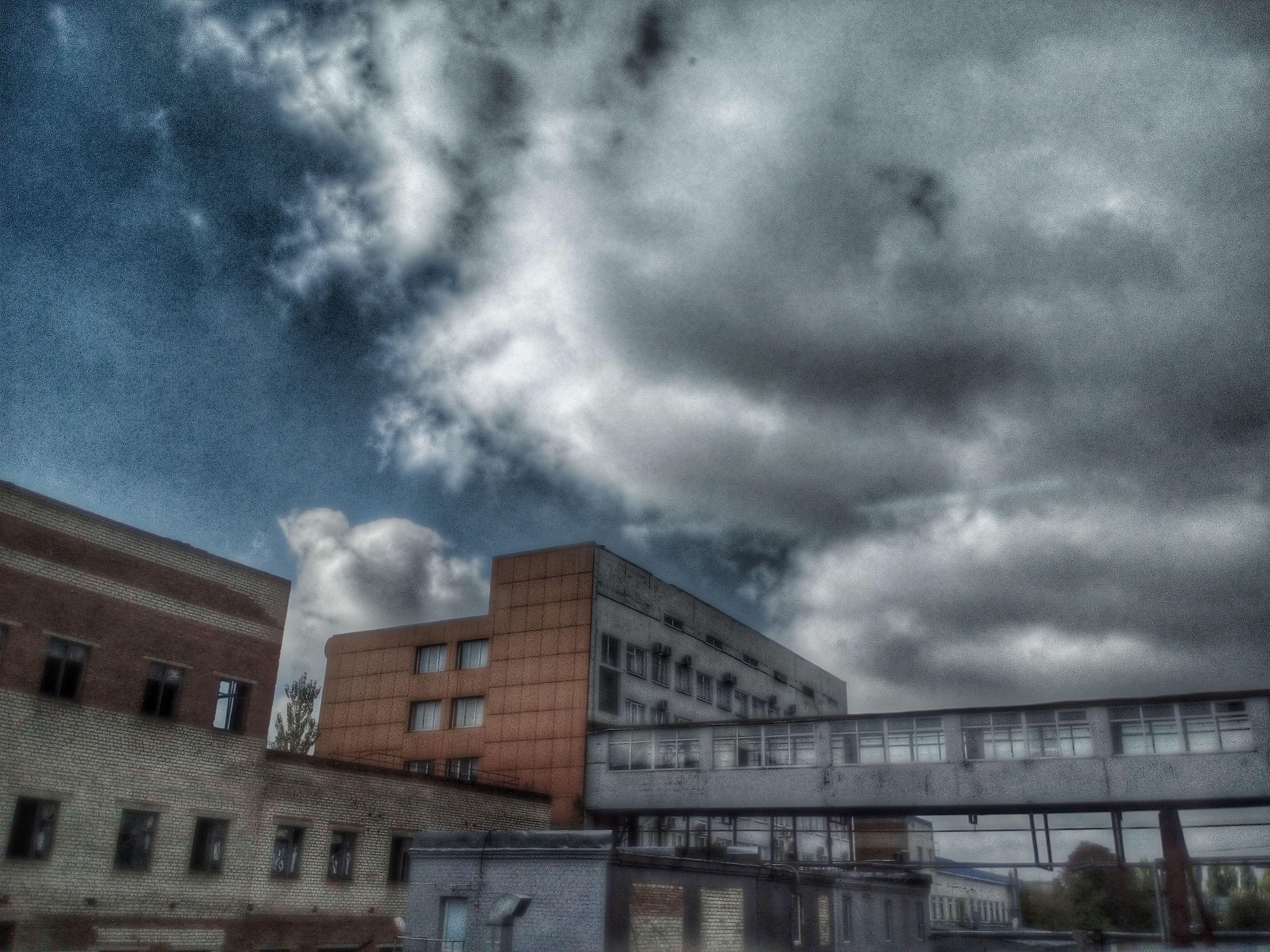 architecture, built structure, building exterior, low angle view, cloud - sky, sky, city, cloud, building, high section, cloudy, day, outdoors, city life, storm cloud, building story, cloudscape, tall - high, no people, office building, residential district, dramatic sky, architectural feature