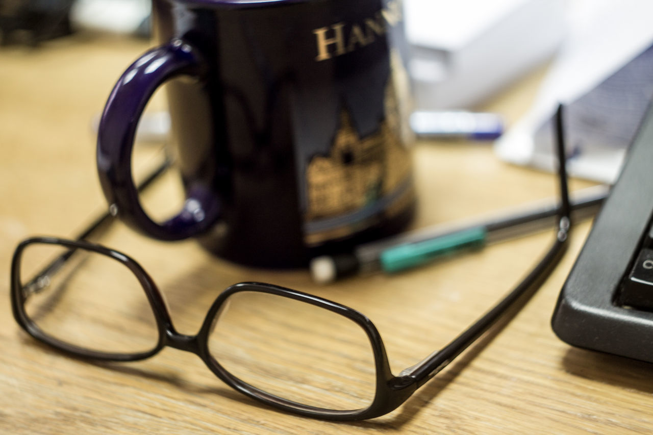 still life, table, indoors, focus on foreground, close-up, eyeglasses, no people, technology, day