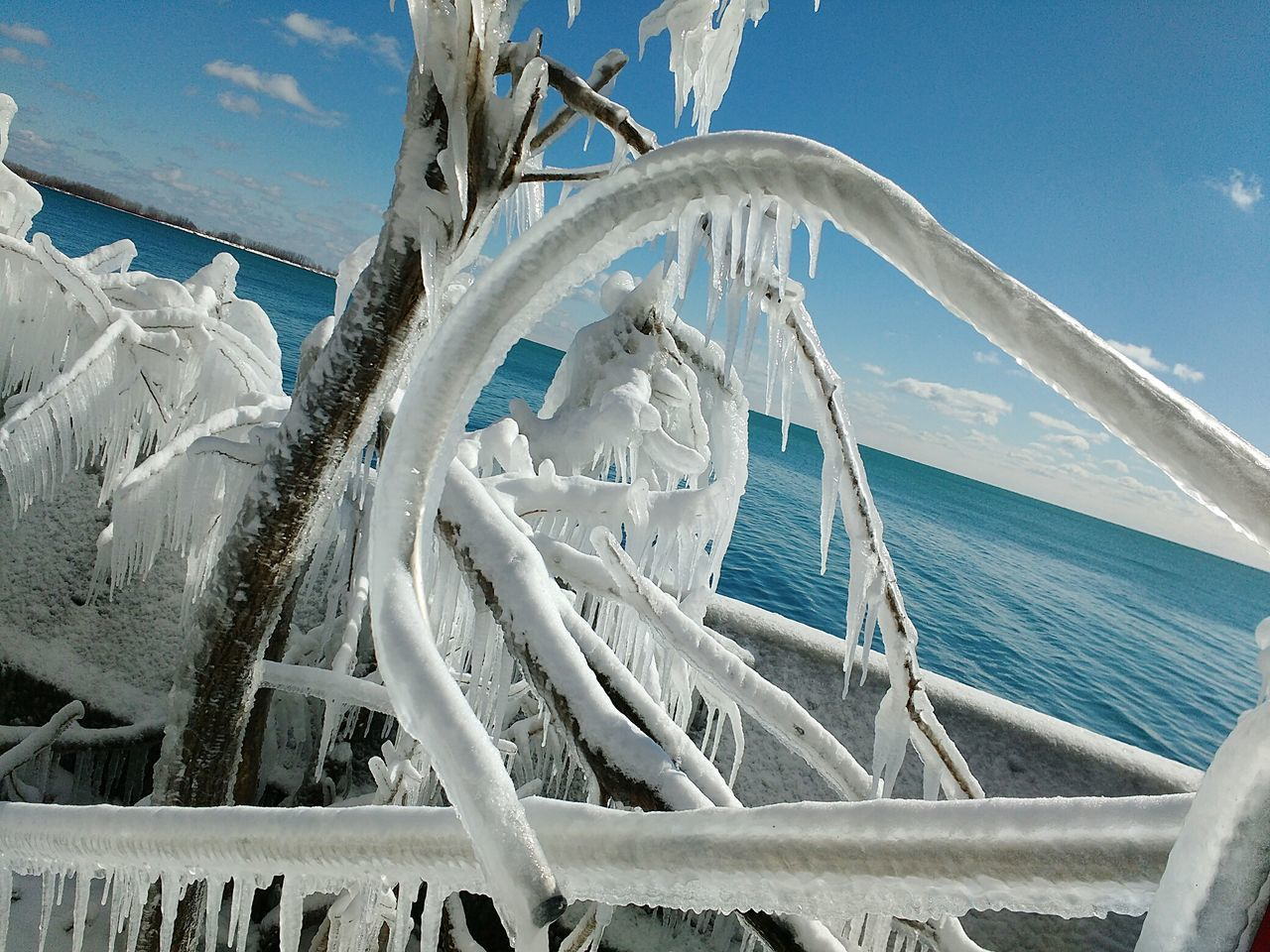 Frozen Driftwood Against Sea During Winter