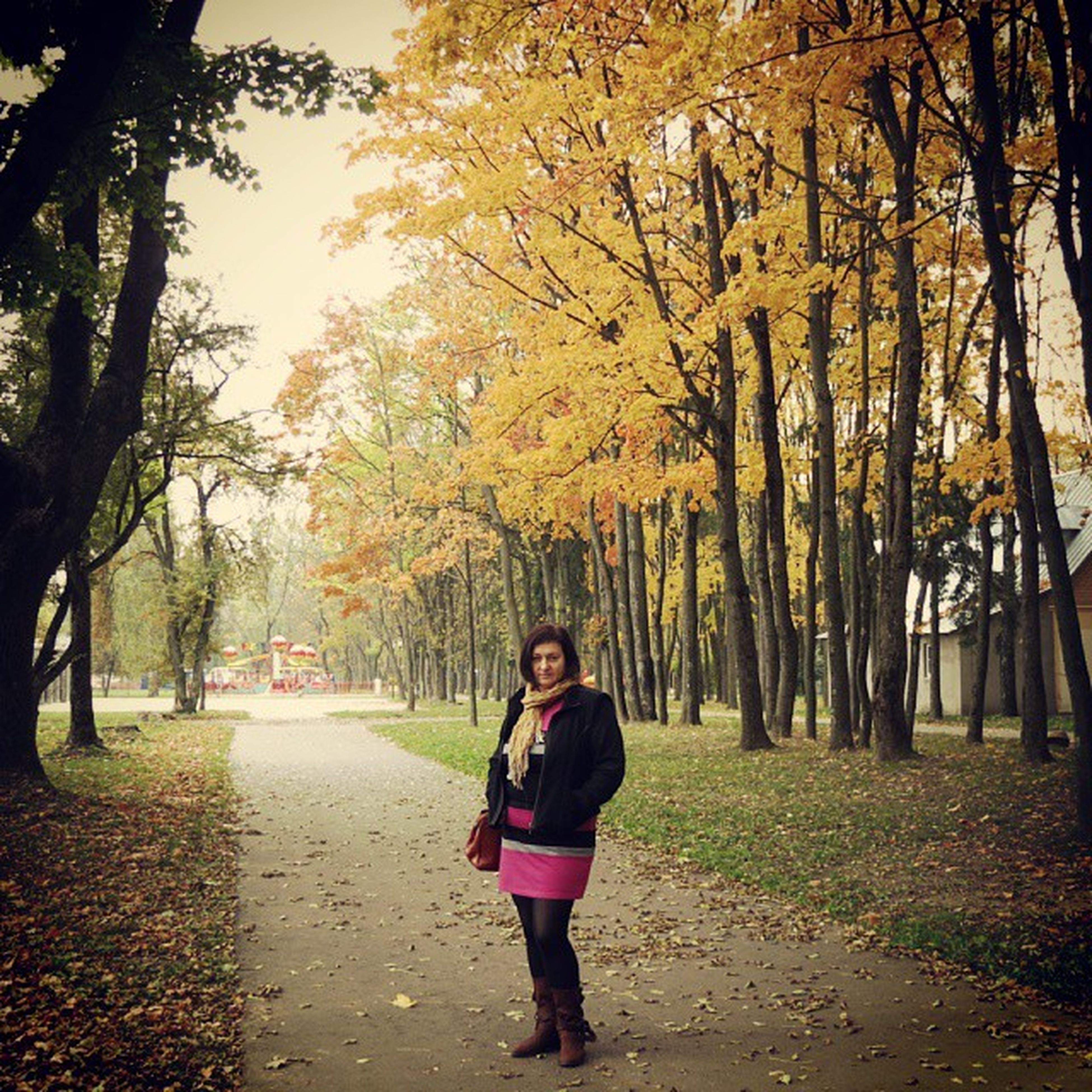 tree, lifestyles, casual clothing, leisure activity, full length, person, front view, looking at camera, autumn, young adult, standing, tree trunk, park - man made space, portrait, change, young women, season, outdoors
