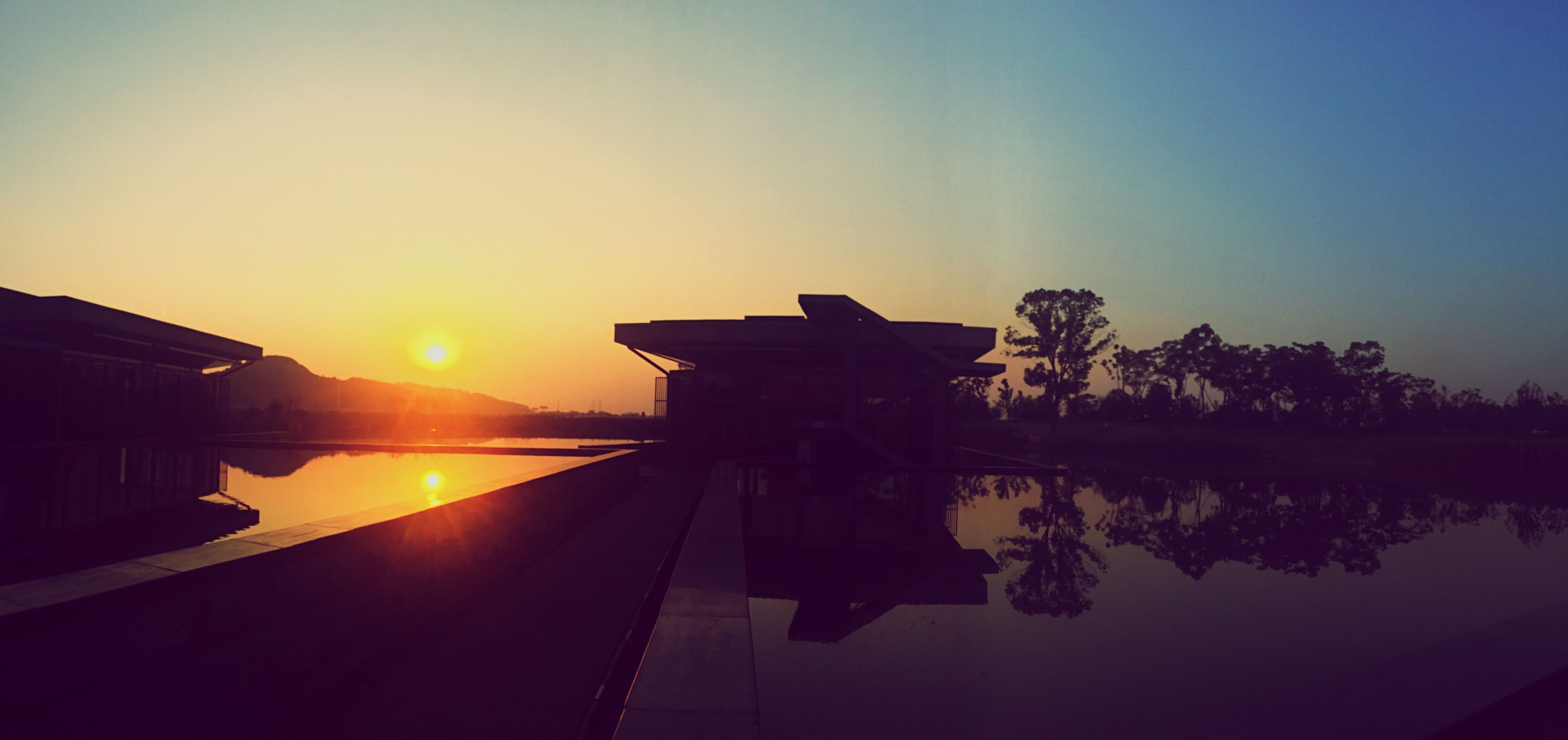sunset, sun, silhouette, reflection, orange color, water, sky, built structure, copy space, clear sky, tranquility, sunlight, scenics, architecture, beauty in nature, nature, tranquil scene, building exterior, lake, railing