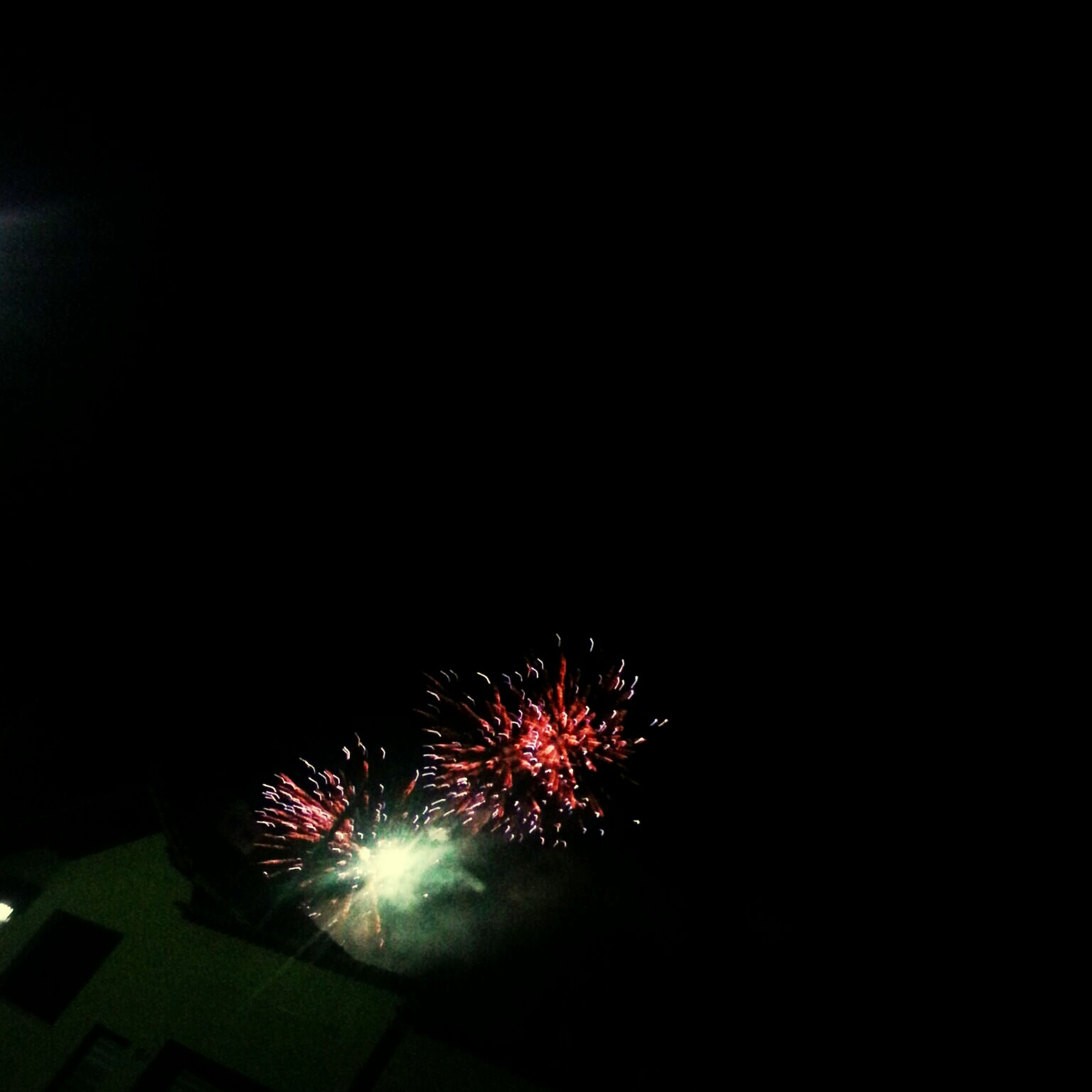 night, illuminated, firework display, celebration, low angle view, long exposure, glowing, exploding, arts culture and entertainment, firework - man made object, motion, sky, sparks, copy space, event, firework, dark, blurred motion, light - natural phenomenon, entertainment