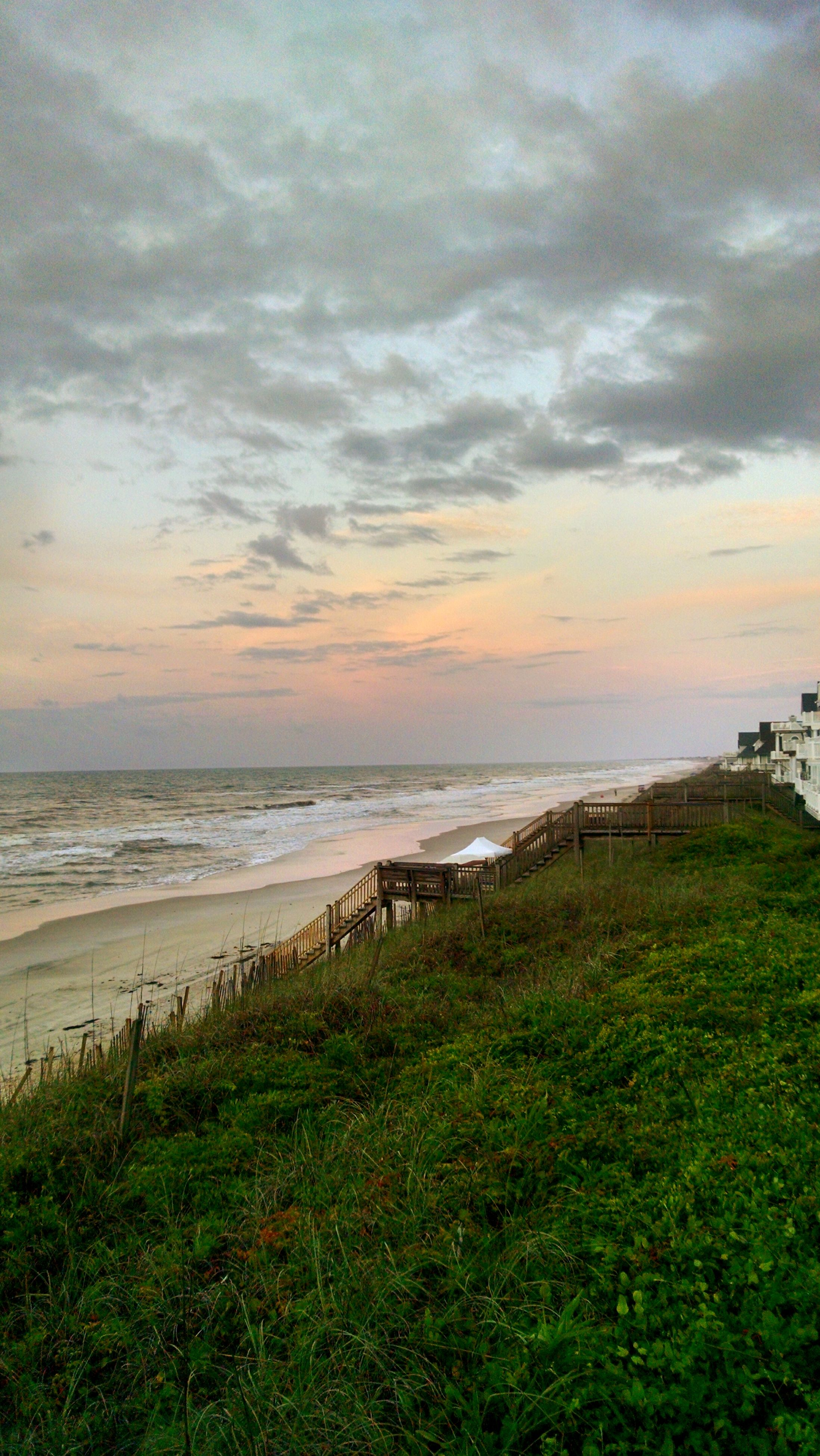 sea, sky, horizon over water, water, scenics, tranquil scene, cloud - sky, beauty in nature, tranquility, beach, grass, shore, nature, cloudy, sunset, cloud, idyllic, coastline, outdoors, plant