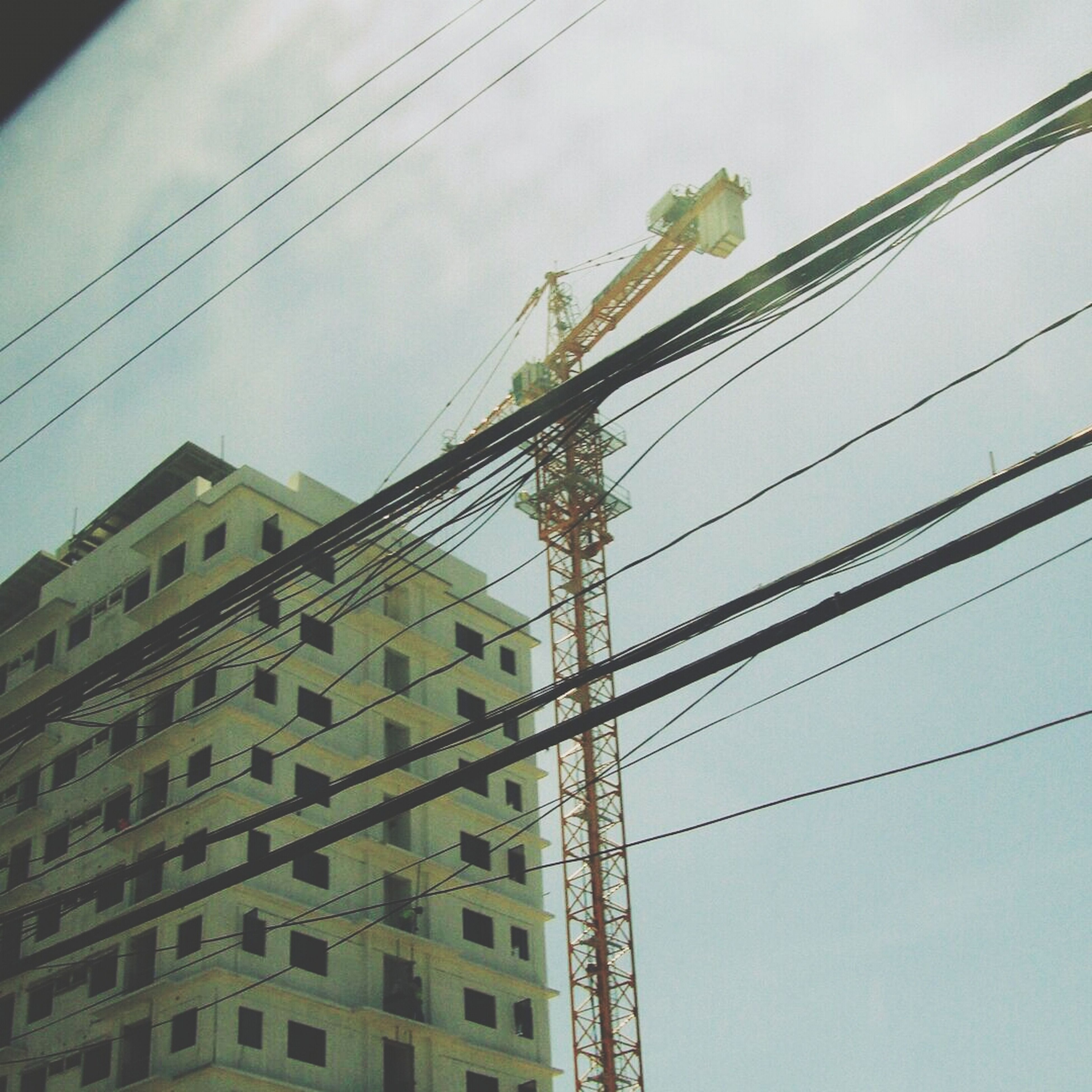 low angle view, power line, electricity pylon, cable, power supply, electricity, connection, built structure, architecture, sky, building exterior, fuel and power generation, technology, power cable, outdoors, no people, day, cloud - sky, complexity, wire