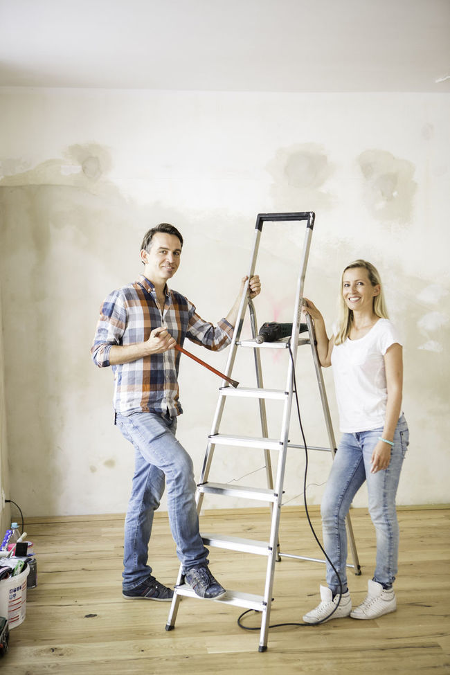 Man and woman standing next to a ladder in a renovated yoga studio Casual Clothing Chequered Shirt Enjoyment Friendship Front View Full Length Fun Jeans Leisure Activity Lifestyles Portrait Renovations Teamwork Yoga Studio