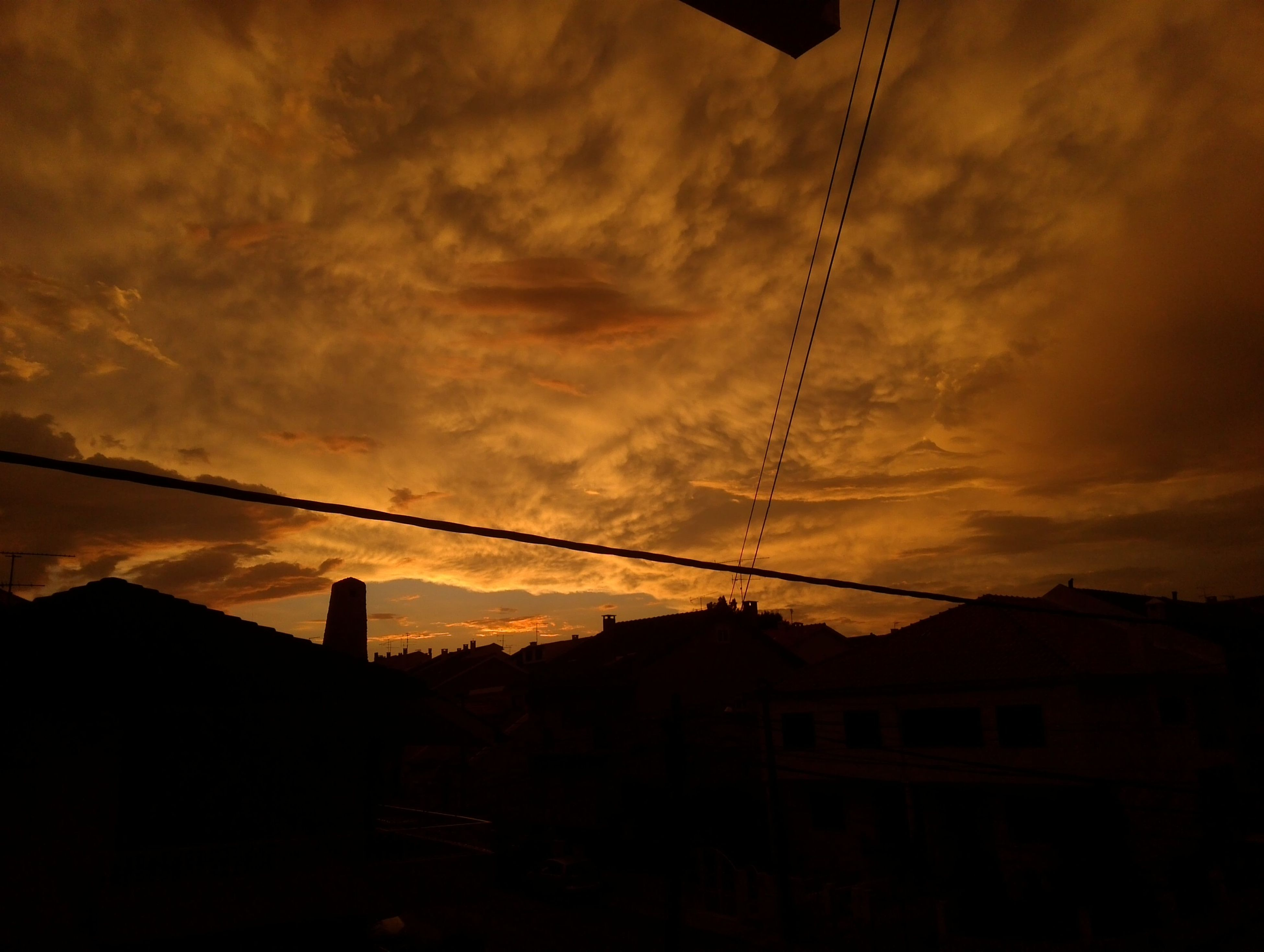 sunset, sky, silhouette, building exterior, built structure, architecture, cloud - sky, power line, house, cloudy, low angle view, orange color, cloud, residential structure, dramatic sky, electricity pylon, beauty in nature, dusk, scenics, nature