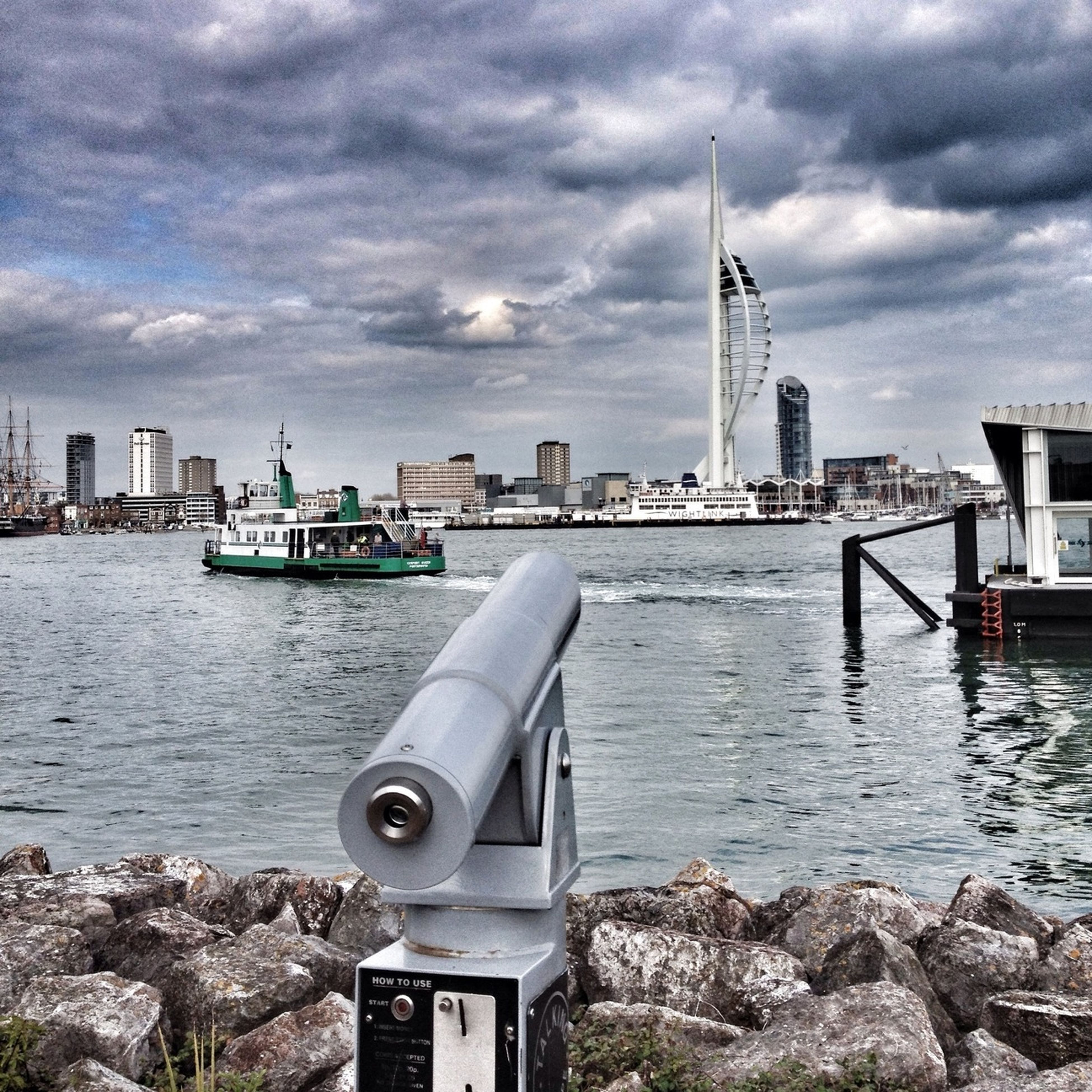 building exterior, architecture, built structure, sky, water, cloud - sky, city, tower, river, cloudy, sea, lighthouse, nautical vessel, cloud, transportation, tall - high, cityscape, travel destinations, day, guidance
