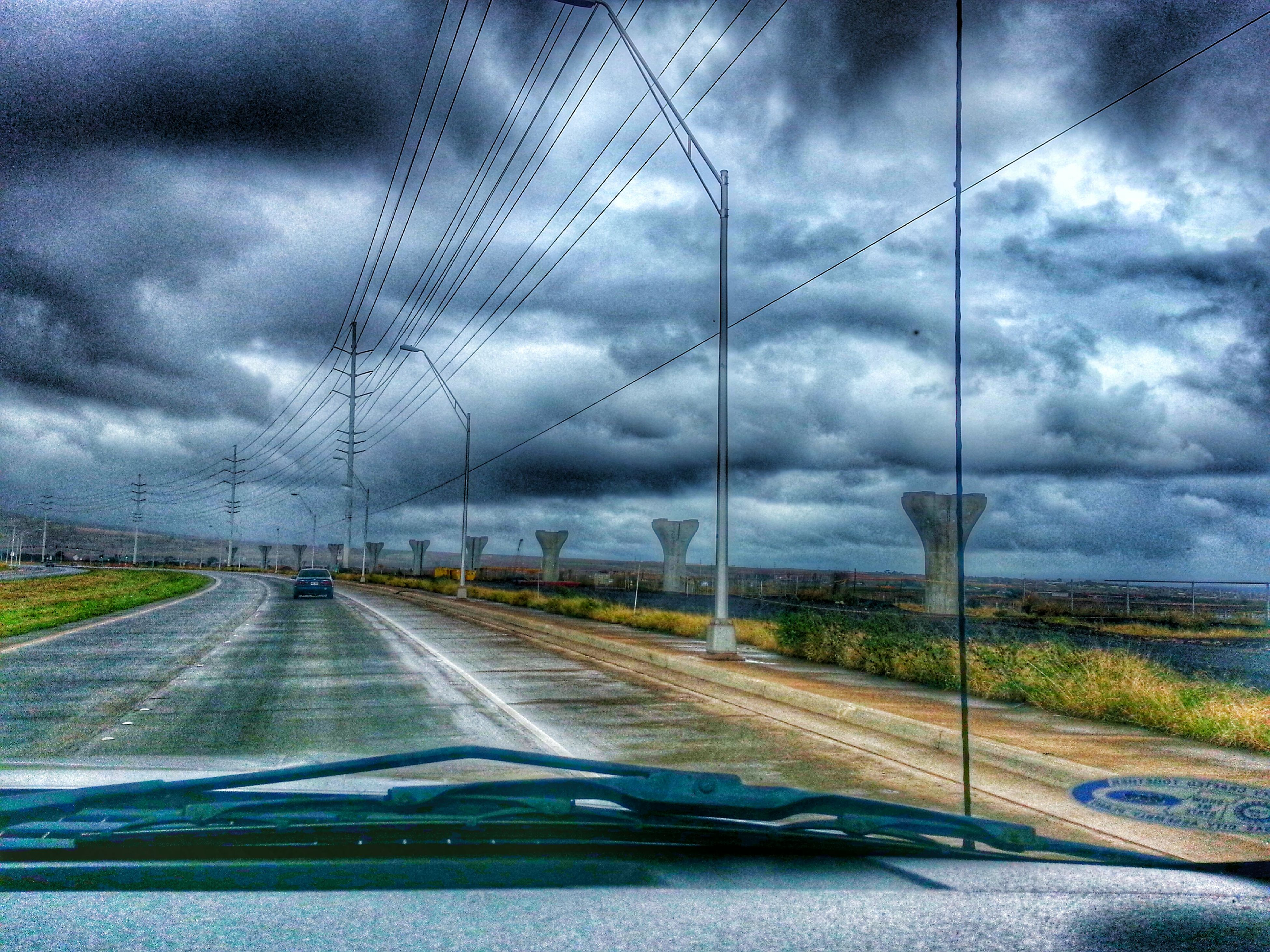 transportation, sky, cloud - sky, cloudy, road, the way forward, cloud, road marking, weather, storm cloud, car, mode of transport, diminishing perspective, overcast, country road, landscape, dramatic sky, vanishing point, windshield, land vehicle