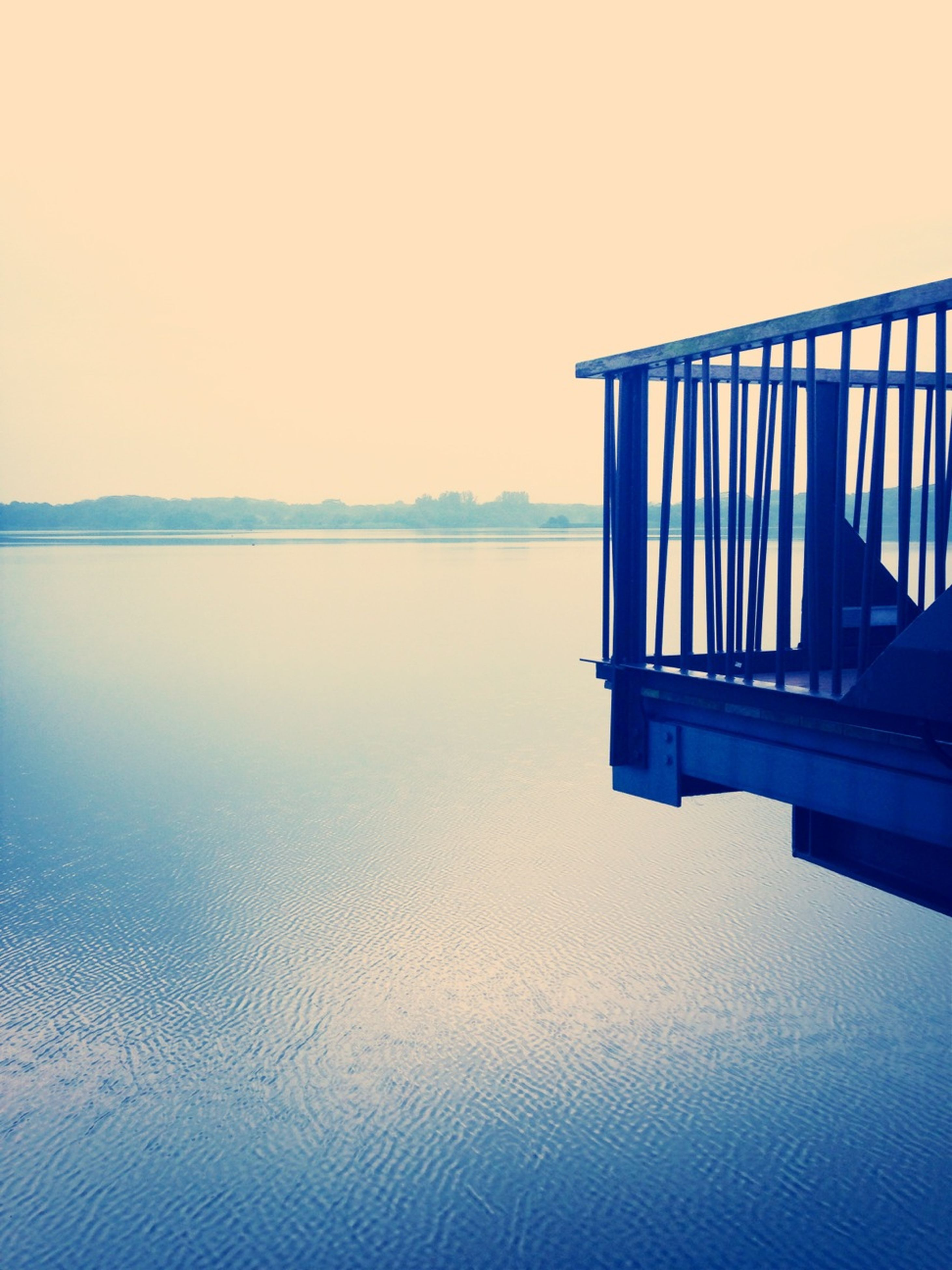 water, clear sky, tranquility, tranquil scene, built structure, lake, scenics, copy space, reflection, architecture, beauty in nature, nature, sea, waterfront, calm, pier, sky, idyllic, blue, no people