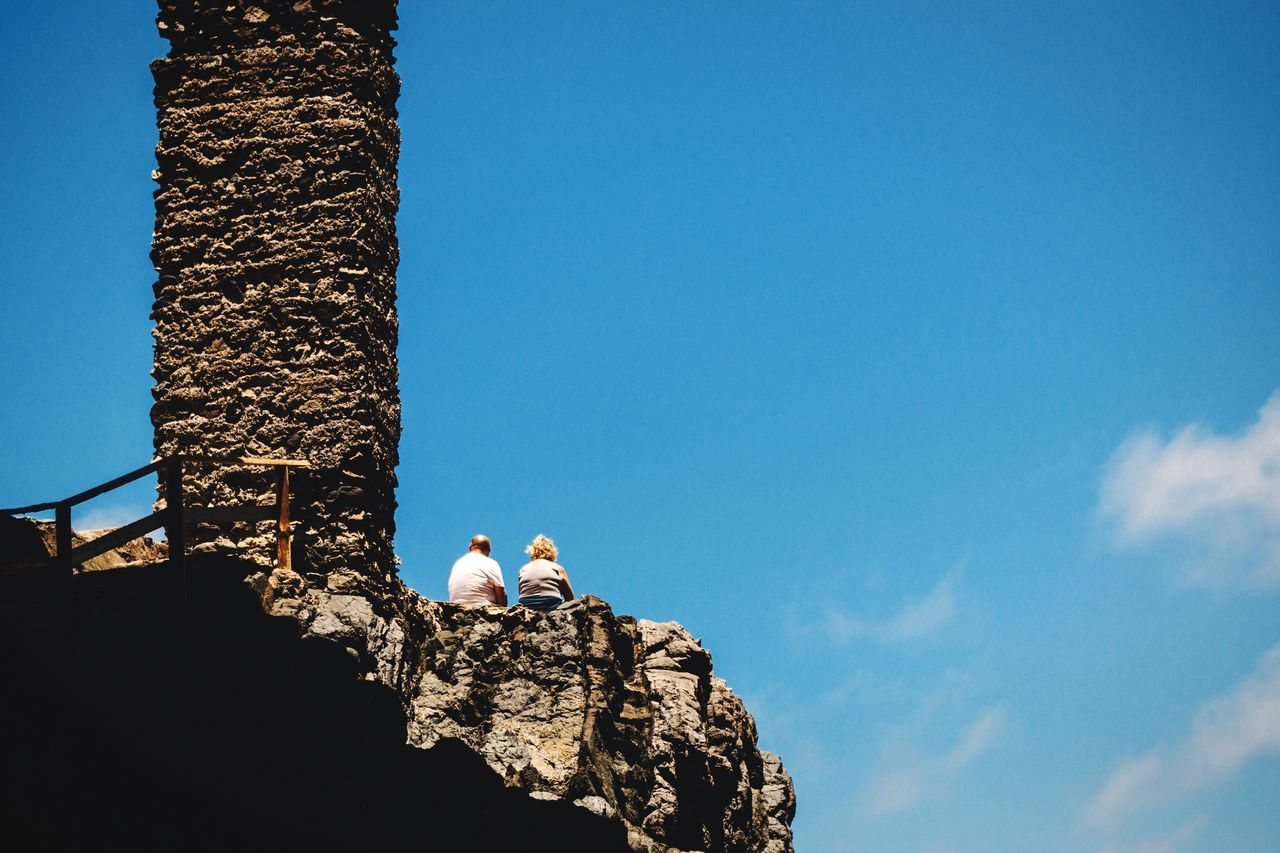 Low Angle View Of Couple Sitting By Column On Cliff Against Blue Sky