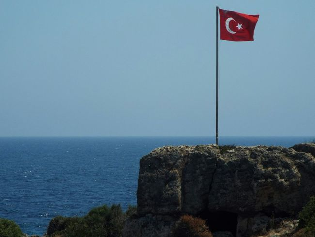 The Turkish flag on Dolphin Island Turkish Flag Flag Rock Blue Water Blue Sky Blue Wave Tourism Tourist Attraction  Travel Photography Travel Destinations Day Trip Sea Mediterranean Sea Boat Trip On A Boat