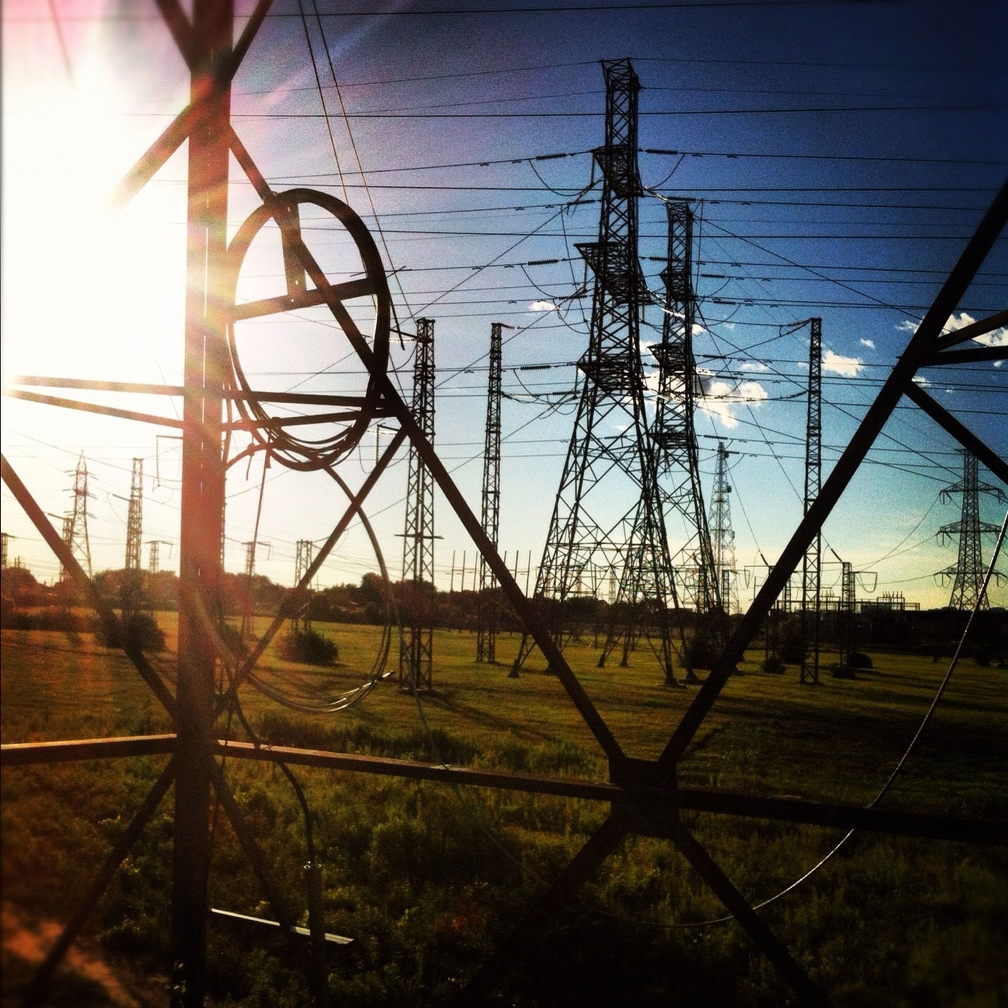 electricity pylon, power supply, electricity, sky, power line, connection, metal, transportation, field, cable, fuel and power generation, fence, grass, no people, outdoors, sunlight, chainlink fence, landscape, day, clear sky