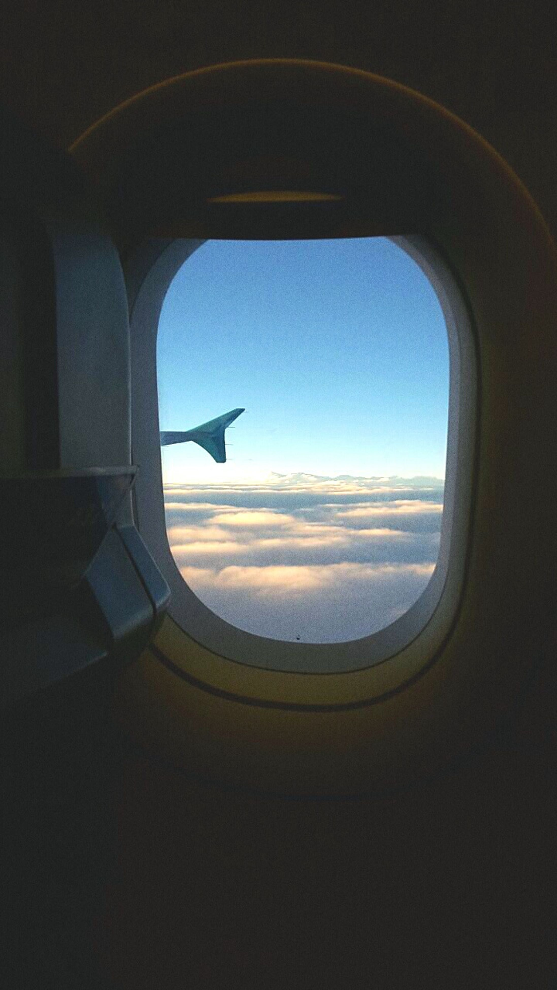 airplane, air vehicle, flying, window, sky, transportation, indoors, aircraft wing, mode of transport, vehicle interior, travel, mid-air, glass - material, cloud - sky, journey, part of, aerial view, transparent, landscape, scenics