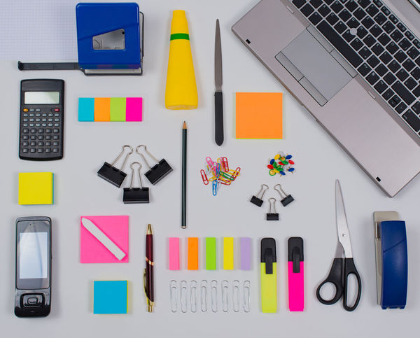 Office Supplies in Flat Lay Still on white background Highlighters Scissors Stapler Calculator Flat Lay Note Notebook Office Supplies Pencil Pens Phone Staples Tacks