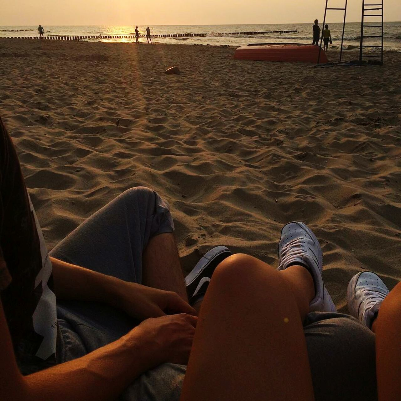 low section, sand, human leg, beach, real people, sitting, barefoot, one person, relaxation, leisure activity, lifestyles, sunset, vacations, water, day, human body part, outdoors, women, nature, sky, adult, people