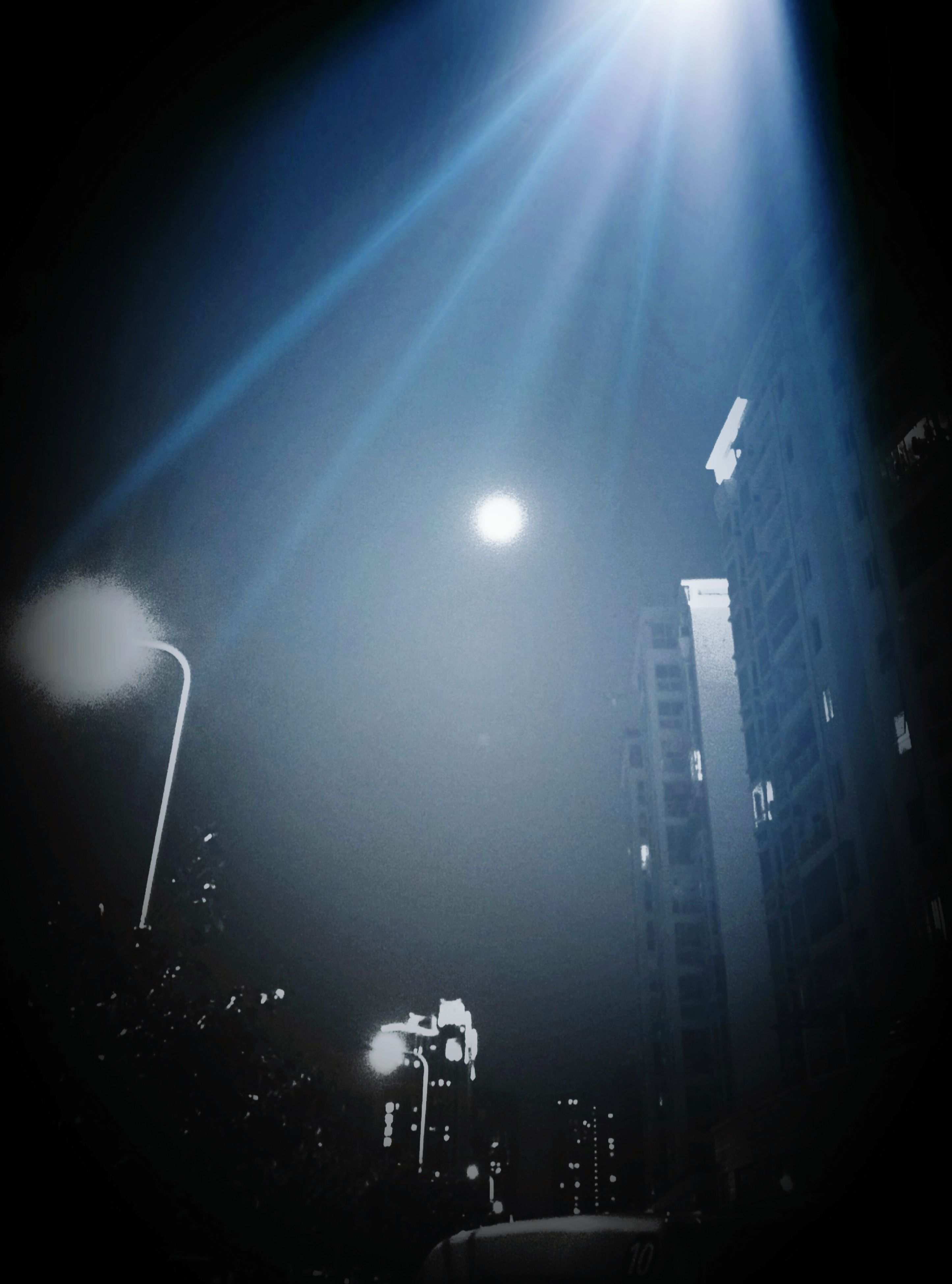 night, illuminated, architecture, building exterior, built structure, city, lighting equipment, light - natural phenomenon, skyscraper, low angle view, modern, street light, sky, light beam, tall - high, no people, glowing, transportation, outdoors, dark