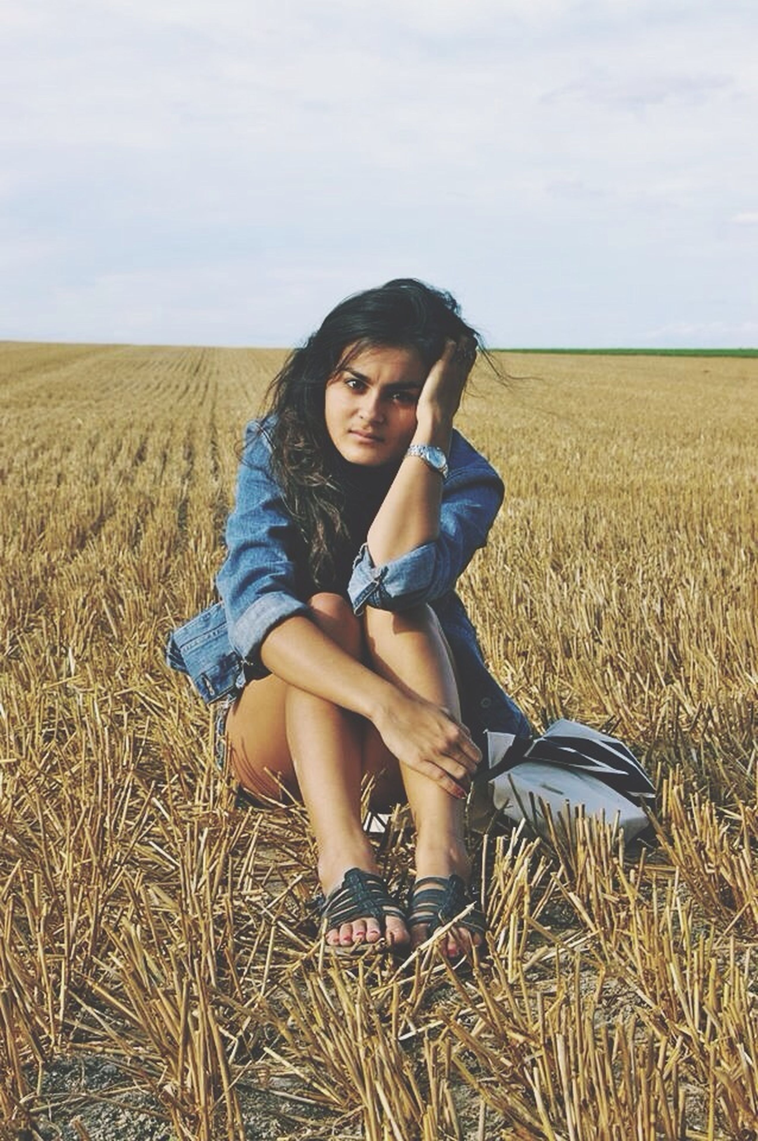 young adult, young women, lifestyles, field, leisure activity, grass, sky, person, casual clothing, landscape, long hair, sitting, full length, relaxation, tranquility, agriculture, nature