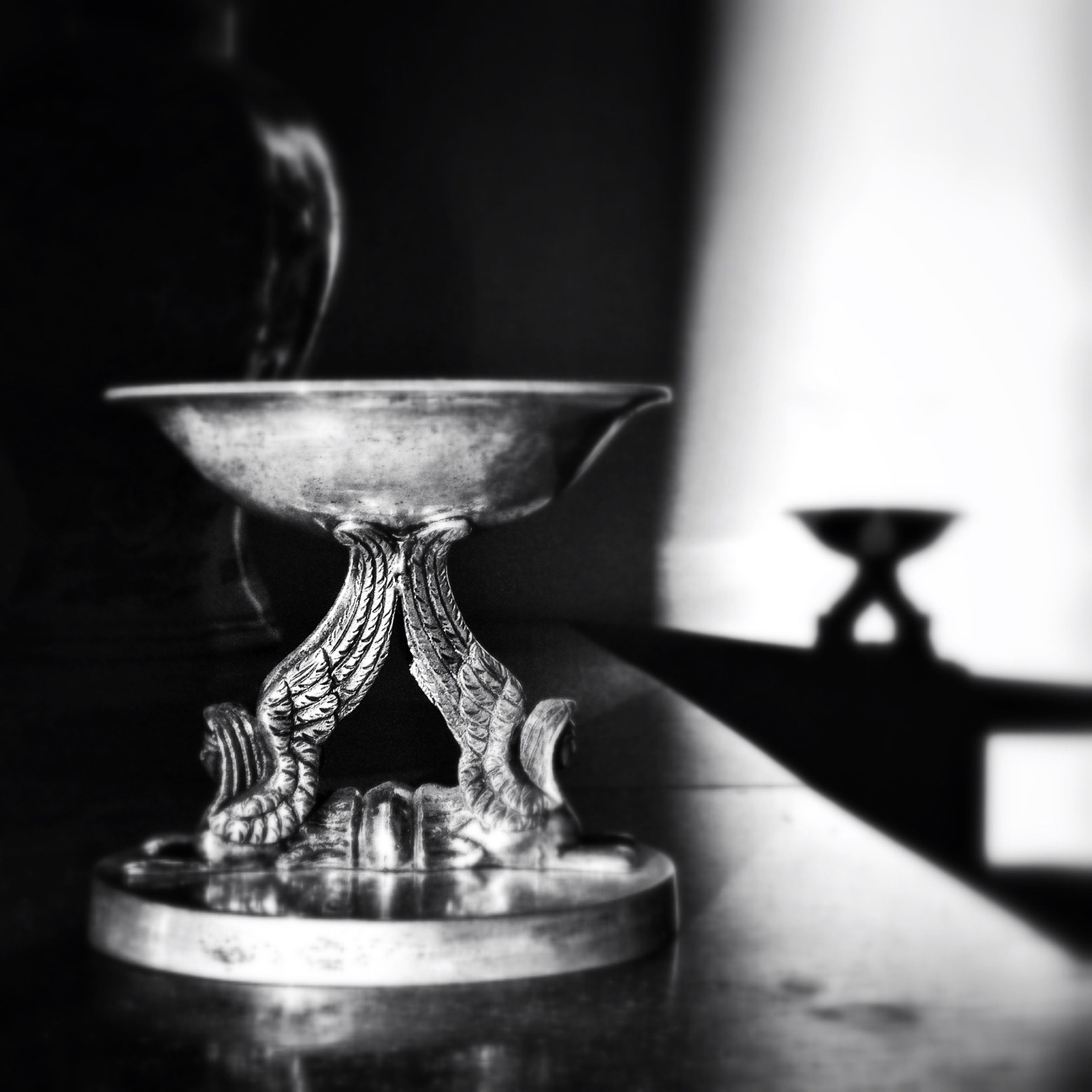 indoors, still life, table, close-up, focus on foreground, candle, glass - material, illuminated, selective focus, lighting equipment, single object, home interior, no people, lit, religion, decoration, wineglass, flame, transparent, glowing