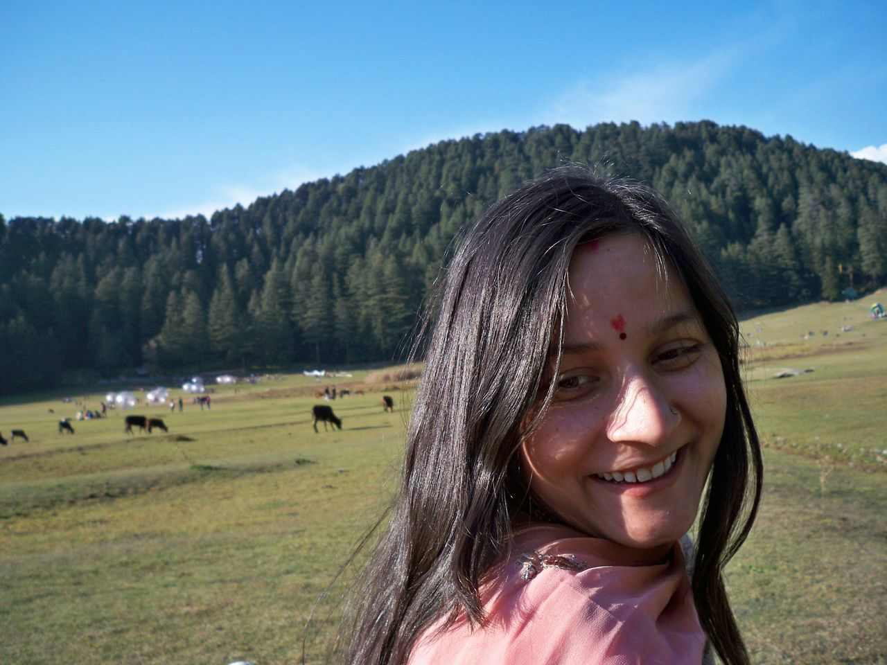 smiling, real people, looking at camera, day, portrait, field, outdoors, nature, landscape, happiness, tree, one person, sky, grass, cheerful, young women, lifestyles, beauty in nature, scenics, young adult, mountain, people