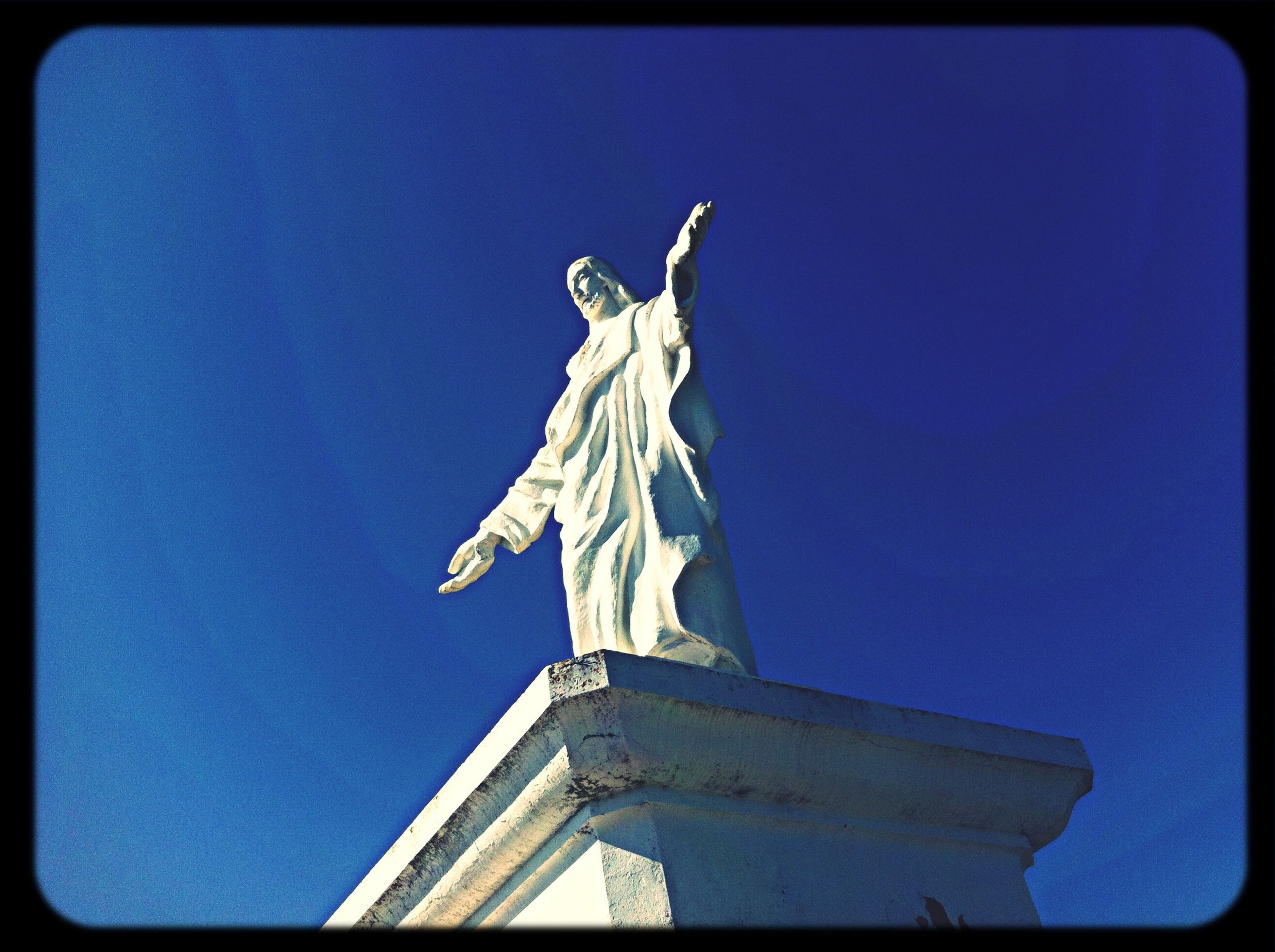 low angle view, statue, sculpture, human representation, transfer print, clear sky, art and craft, blue, art, creativity, auto post production filter, copy space, built structure, animal representation, architecture, sky, day, no people