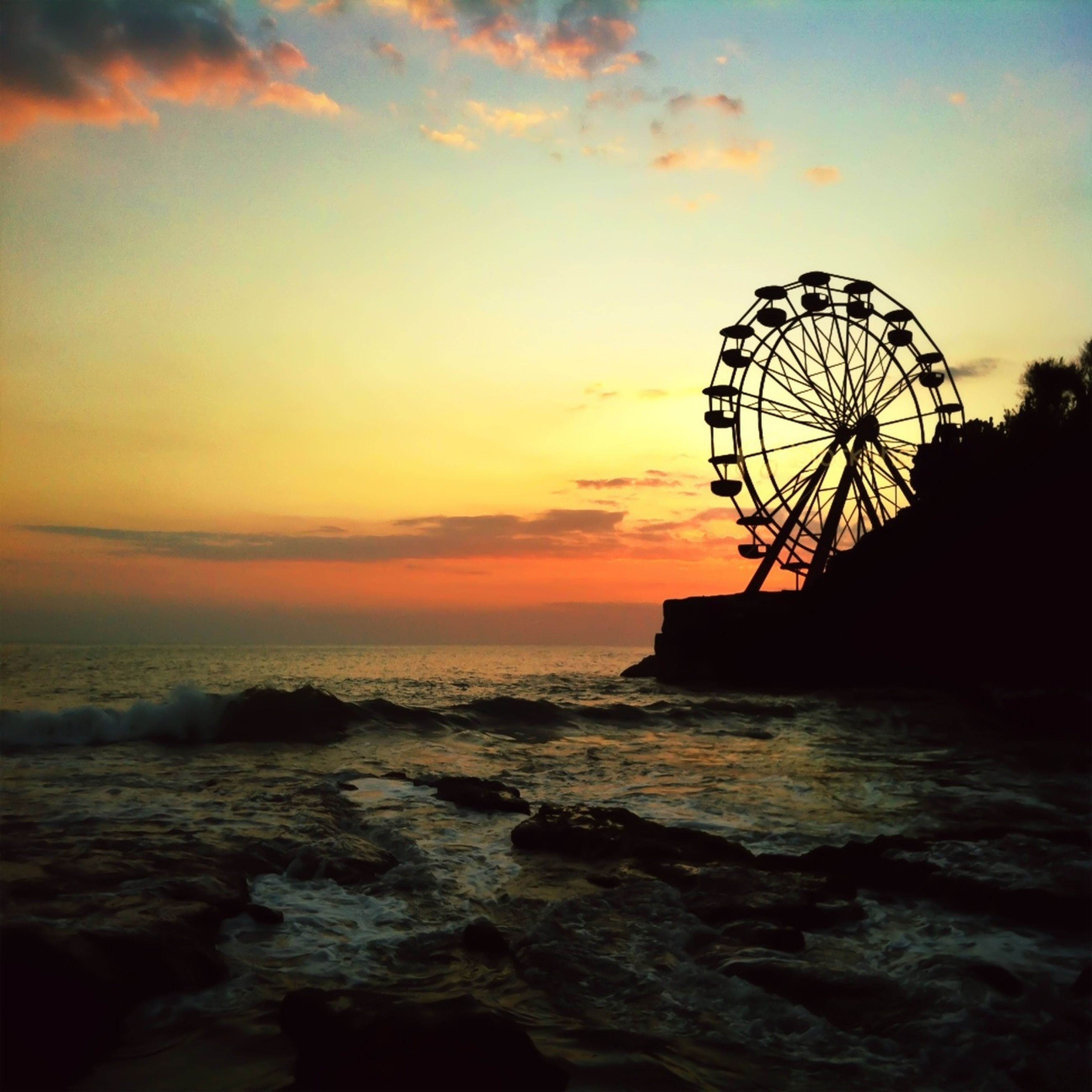 sunset, sea, sky, water, silhouette, horizon over water, beach, ferris wheel, scenics, cloud - sky, tranquil scene, orange color, beauty in nature, tranquility, shore, nature, dusk, cloud, idyllic, amusement park