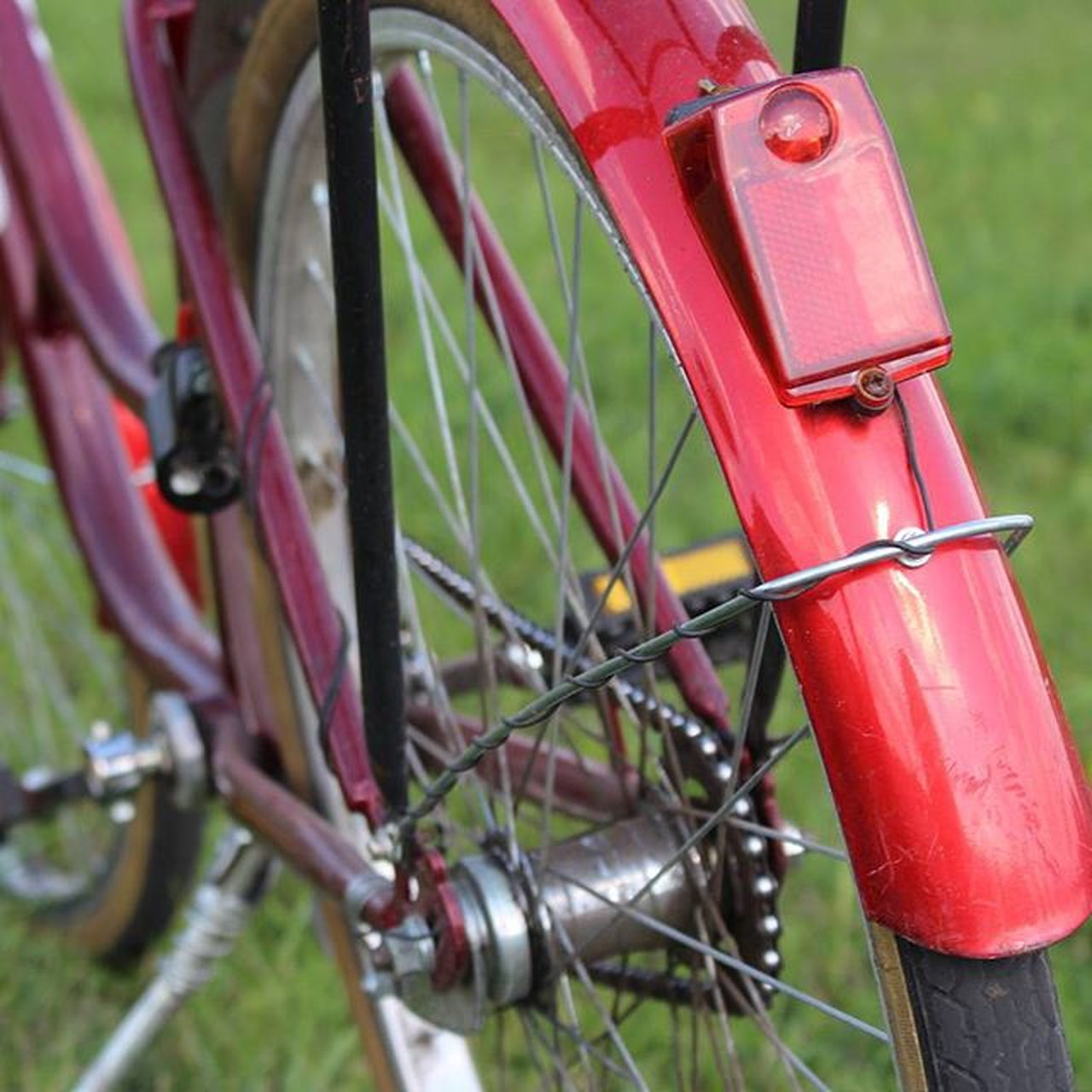 bicycle, transportation, red, stationary, outdoors, day, no people, mode of transport, grass, land vehicle, wheel, close-up