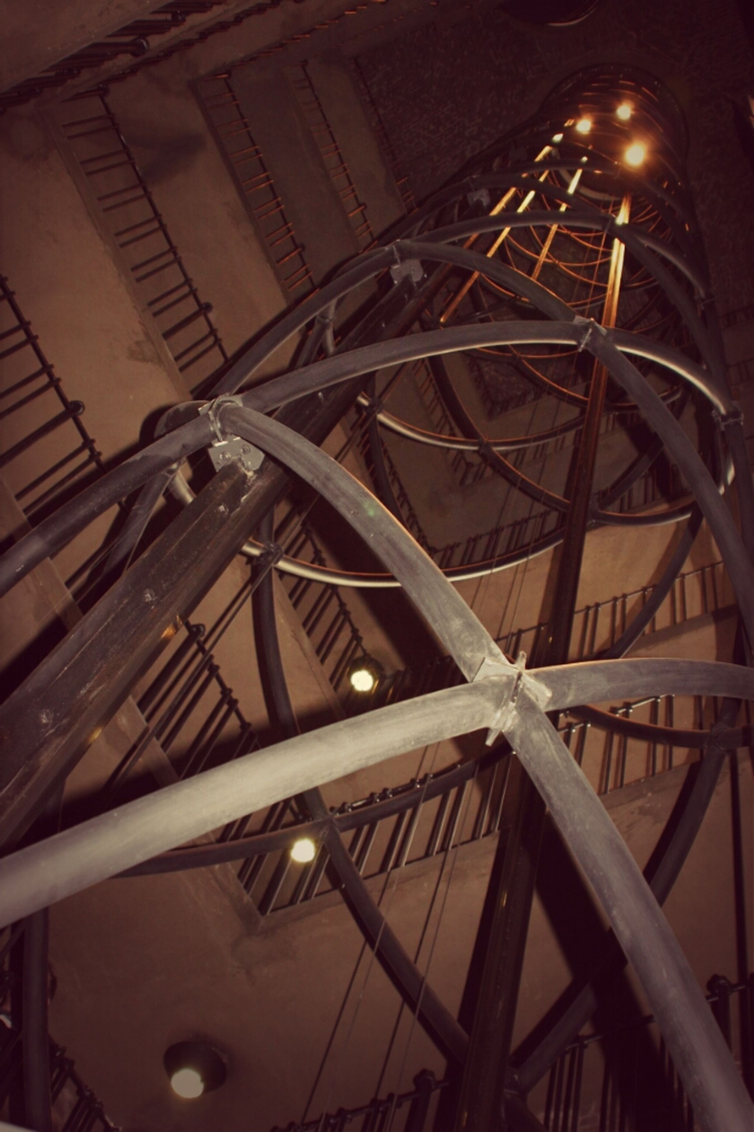 low angle view, indoors, metal, built structure, night, architecture, illuminated, metallic, transportation, no people, engineering, ceiling, circle, railing, wheel, high angle view, pattern, geometric shape, bridge - man made structure