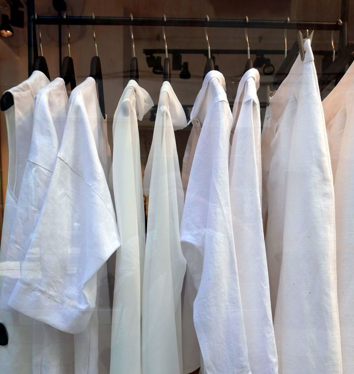 White cloths hanging view through the window of a store Clothes Store Window Shoping White