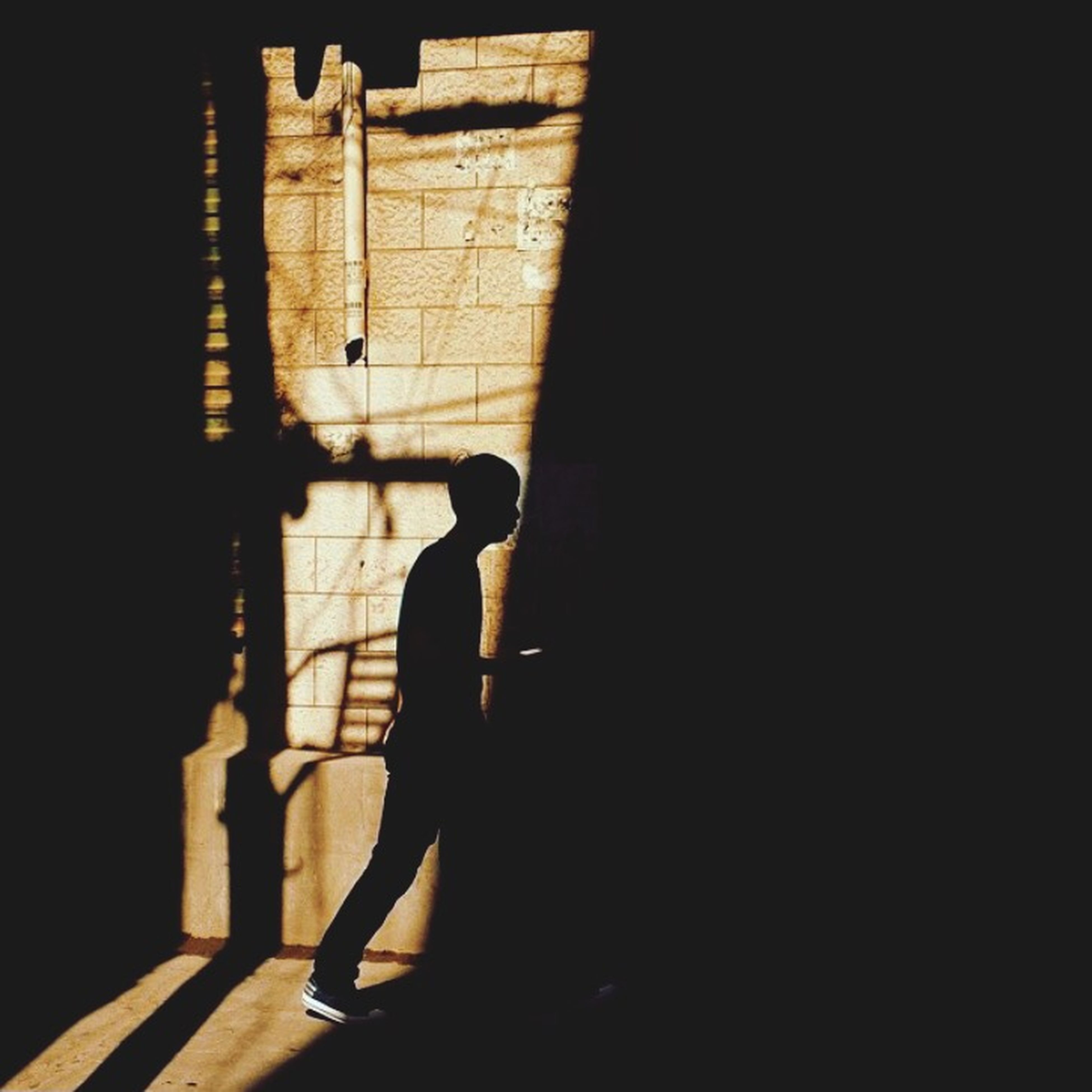 indoors, silhouette, lifestyles, shadow, full length, standing, dark, men, leisure activity, person, walking, wall - building feature, low section, rear view, night, side view, sunlight